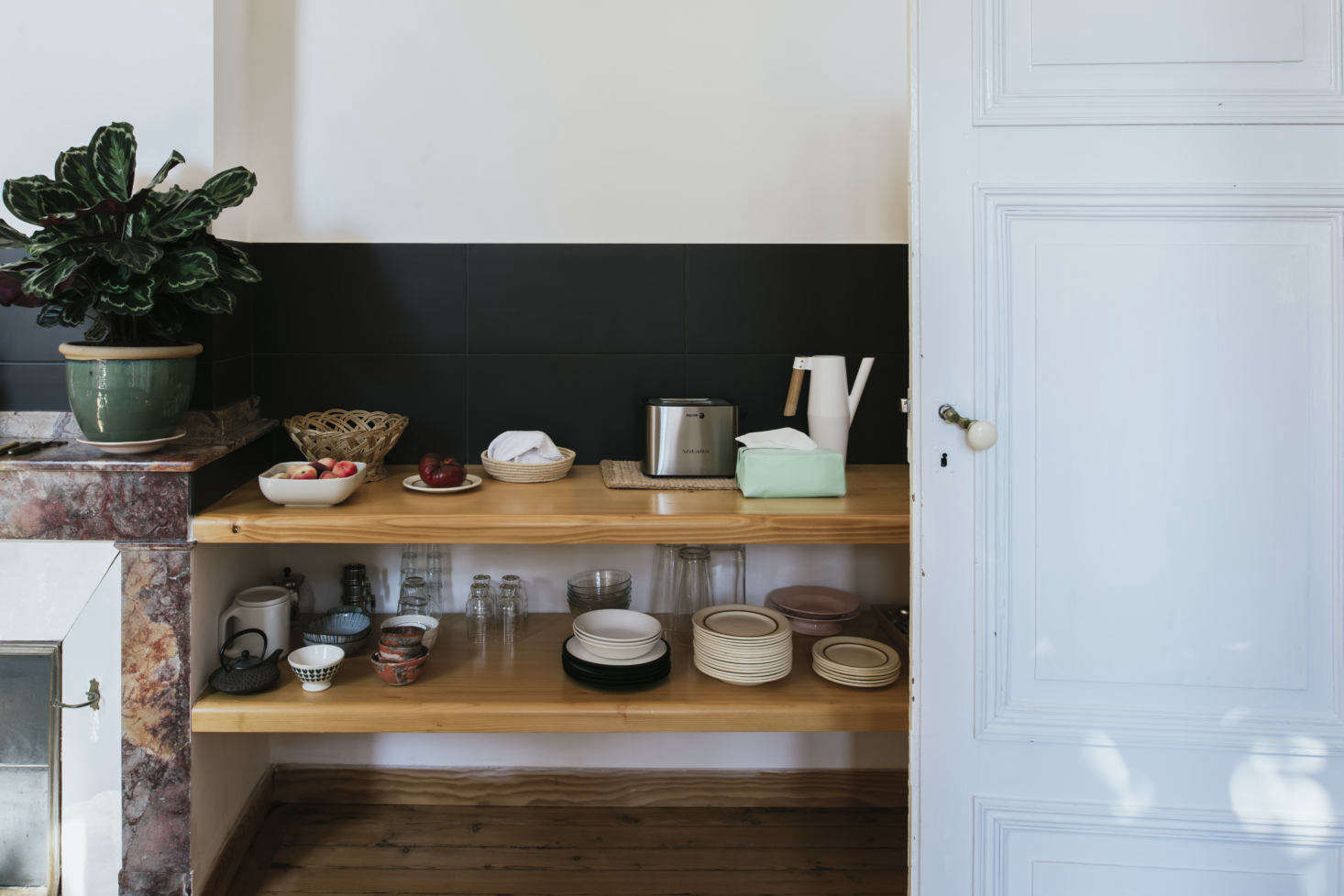 """On display are Sathal's collections. """"These are dishes that I find mostly in flea markets, and when my boyfriend travels, he brings me back finds from different countries,"""" she says. """"I find tea towels in the vide-greniersand I also make linens."""" The low black backsplash is made of Italian tiles."""