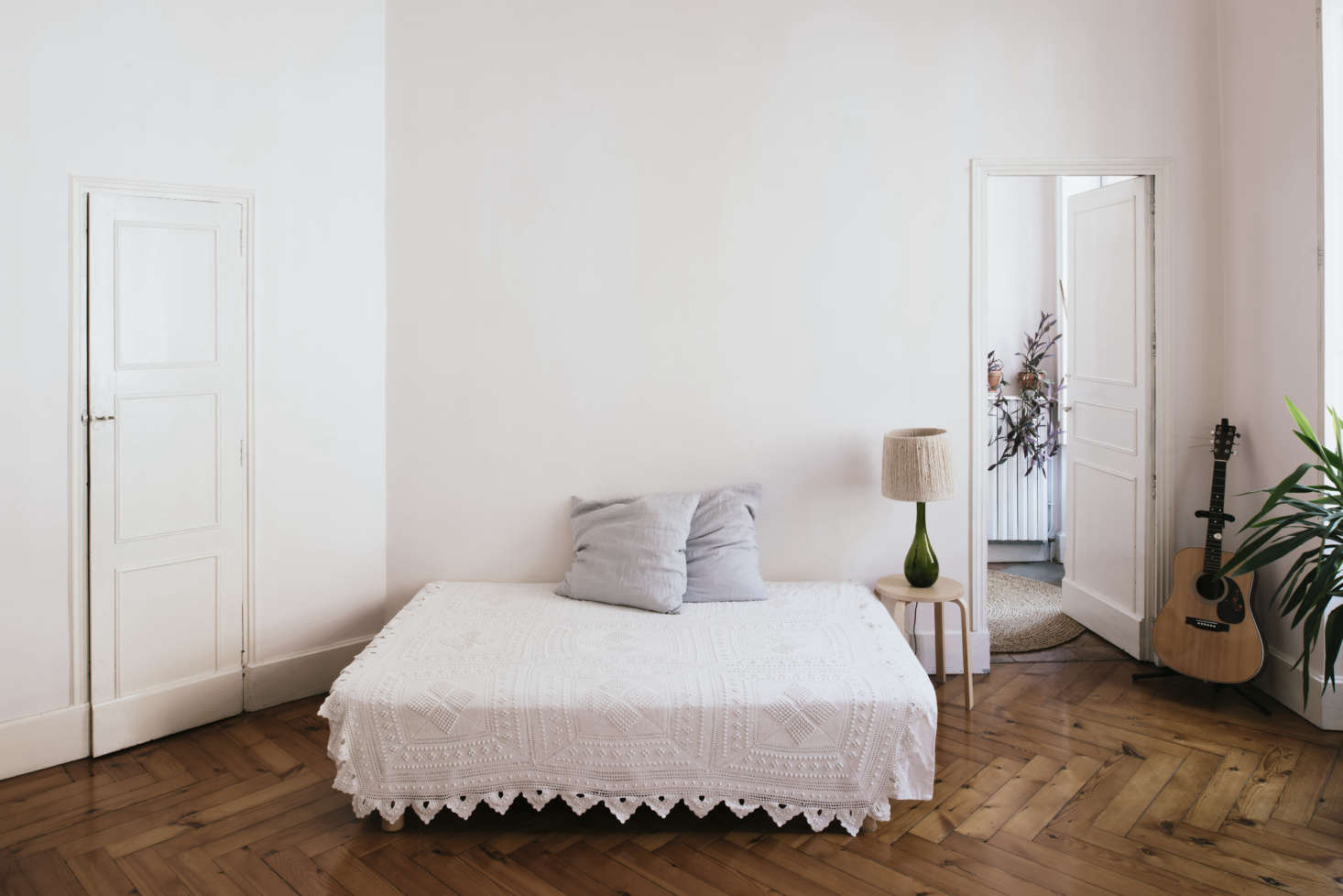 """The sparsely fitted bedroom. """"This room and Kélit's room are a continuation of the living room with the white sofa,"""" Sathal says. She found the torn crocheted blanket at a flea market and repaired it herself."""