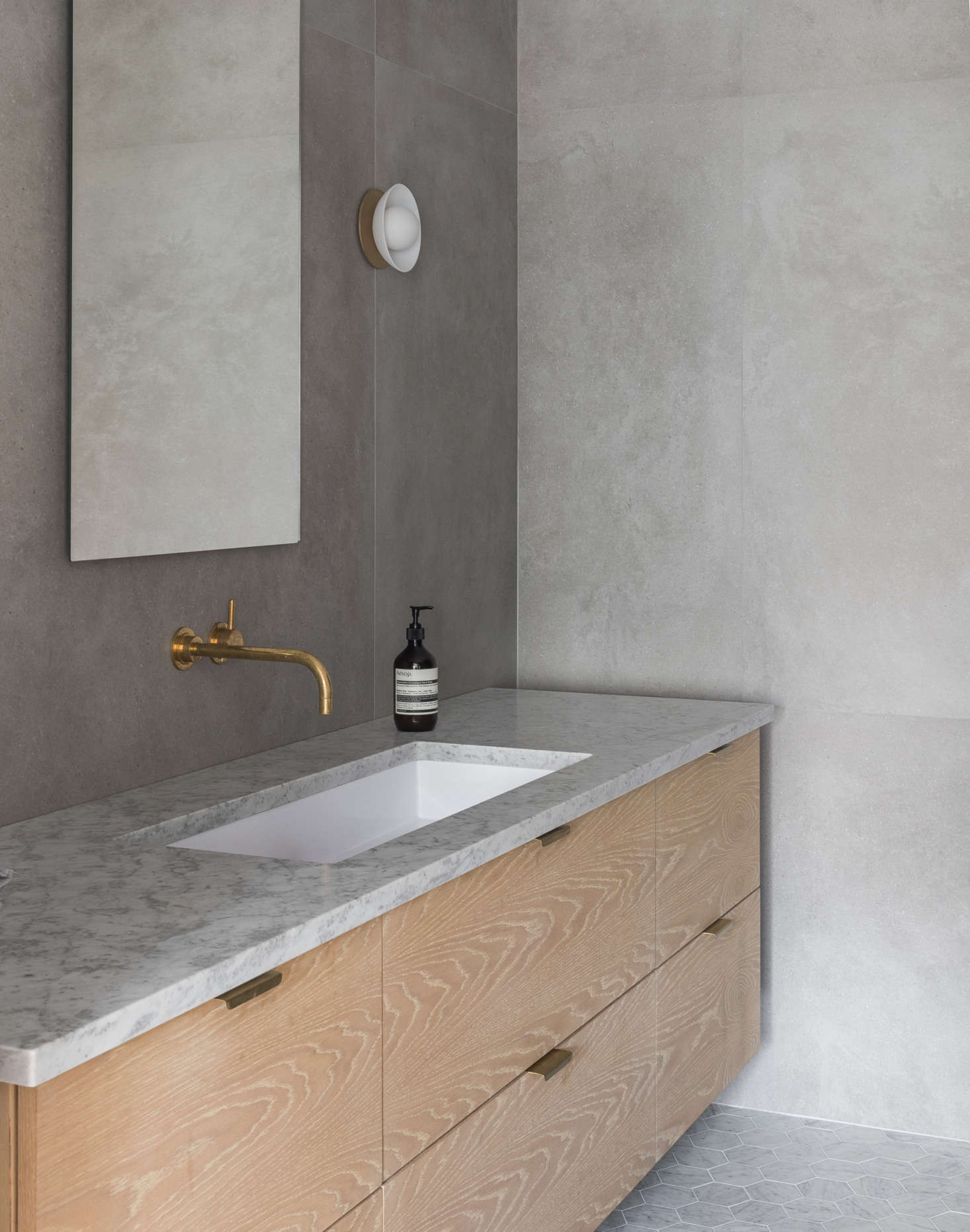 The architects used Nemo's large-format Area porcelain tiles on the walls. The floating vanity countertop echoes that of the kitchen—honed Carrara marble. The faucet is from California Faucets and the sconce is Allied Maker's Flush Dome.