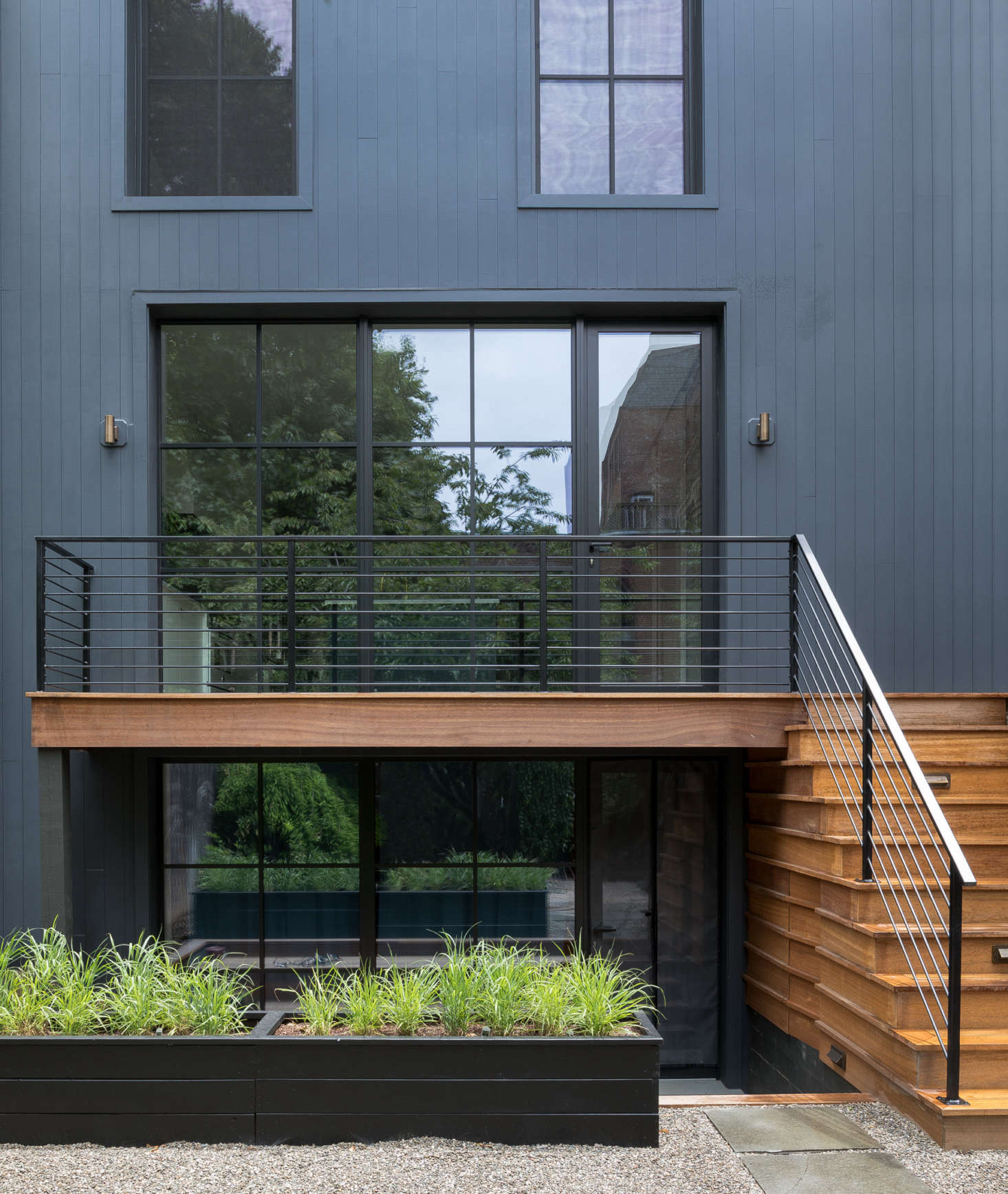Modern steel railings complement the new steel windows on the back wall, which continue down to the garden level (that space was converted into a separate apartment for the homeowners' parents or a future rental). The architects used Boral's Truexterior vertical siding with a nickel gap joint for the exterior cladding and mahogany wood for the new deck.