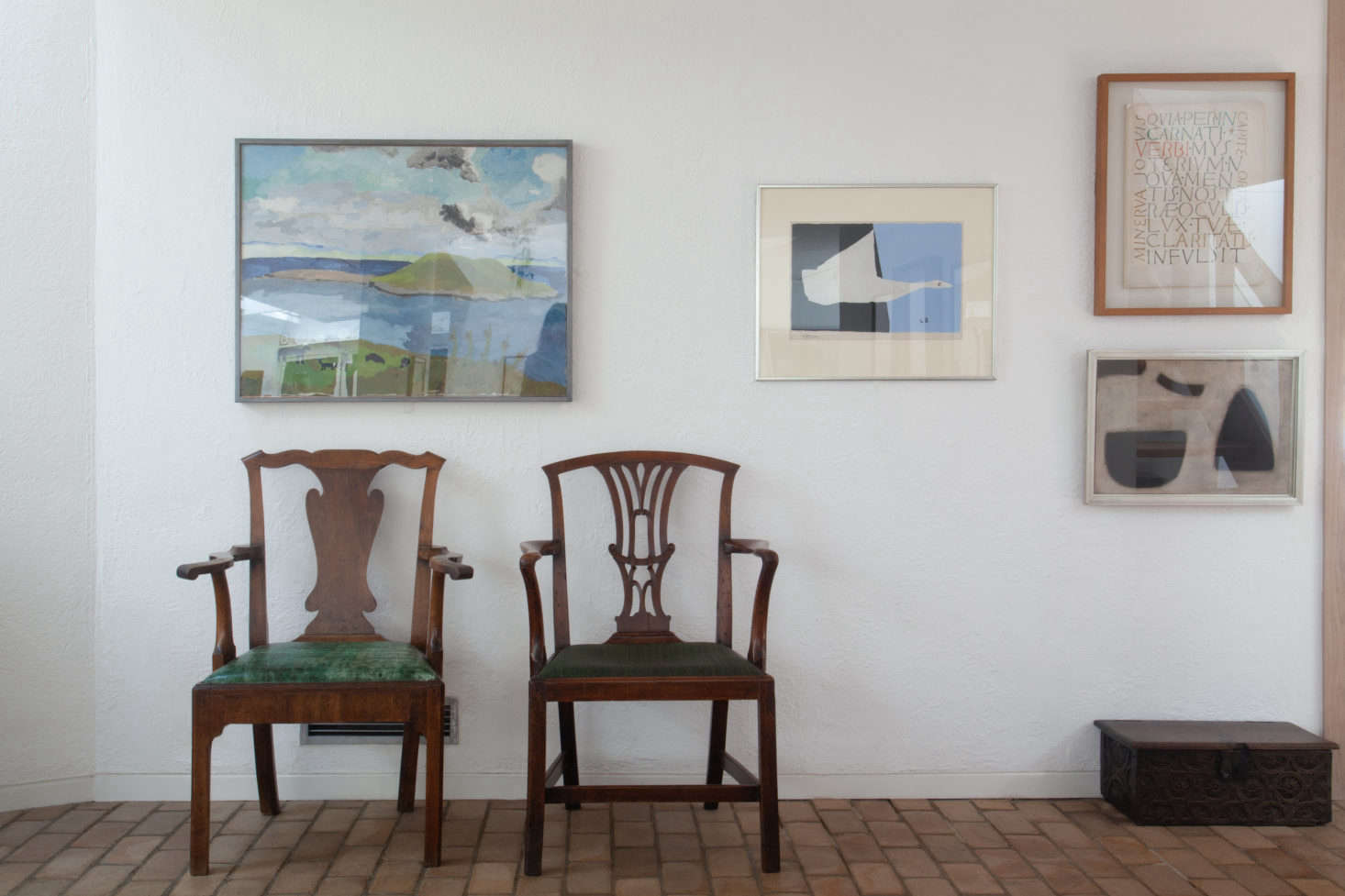 A pair of mismatched armchairs, both with green upholstered seats, are positioned in the gallery extension for guests to view paintings on the opposite wall.