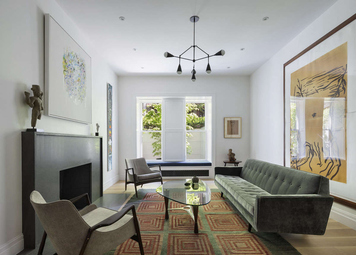 Art plays the starring role in this room, while the fireplace provides a note of contrast to the gallery-white walls without calling attention to itself. Photograph by Michael Moran, courtesy of O&#8