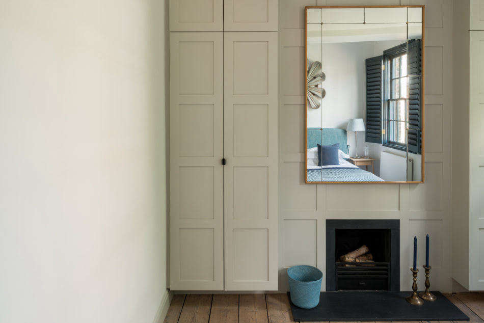 A petite black slate fireplace is incorporated into the wall paneling in the bedroom of a home on historic Roupell Street in London. Photograph courtesy of The Modern House fromA Rescued Georgian in a &#8