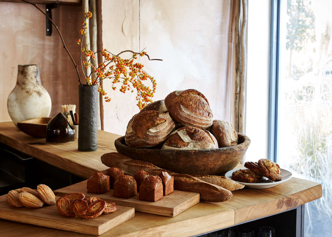 Madeleines, financiers, palmiers and Naroques bread made from French grains on the wooden counter.