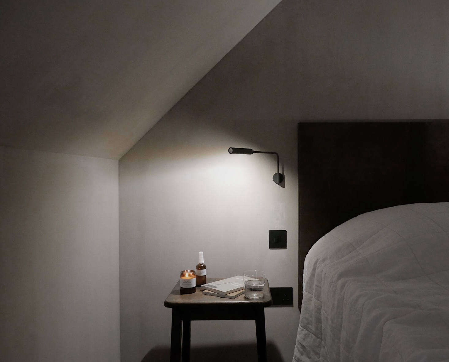 """The beds have custom leather headboards and bedsideFlo LED Wall Lights by Foster & Partners. On the side tables: reading materials as well as naturally scented candles and """"comfort mists"""" by UK company Honest."""
