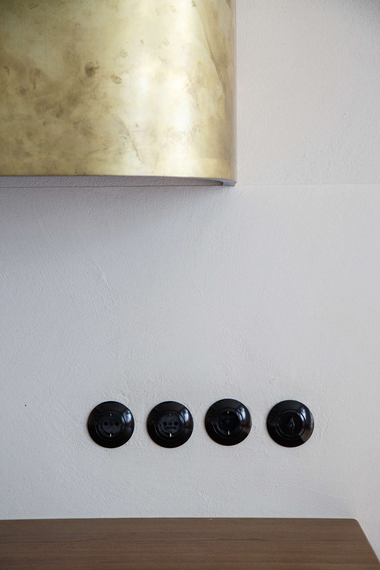 The black bakelite electrical outlets and light switches are from Berker of Germany's Bauhaus-inspired Serie 1930 line.