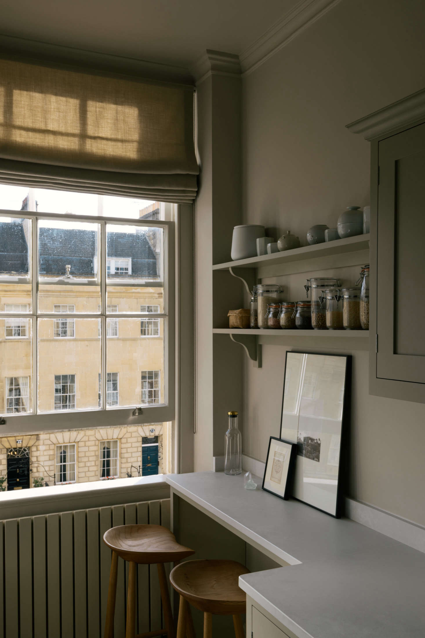 "The wall-hung radiator is painted the same Cornforth White as the walls. A local curtain maker stitched the Roman shade in a French linen, which Rosa points out, is in a ""Bath stone hue"" to match the view out the window."