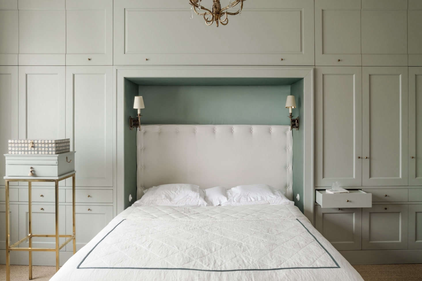 To add much-needed storage in the bedroom, Chrapka designed a wall of built-ins, painted in Farrow & Ball&#8