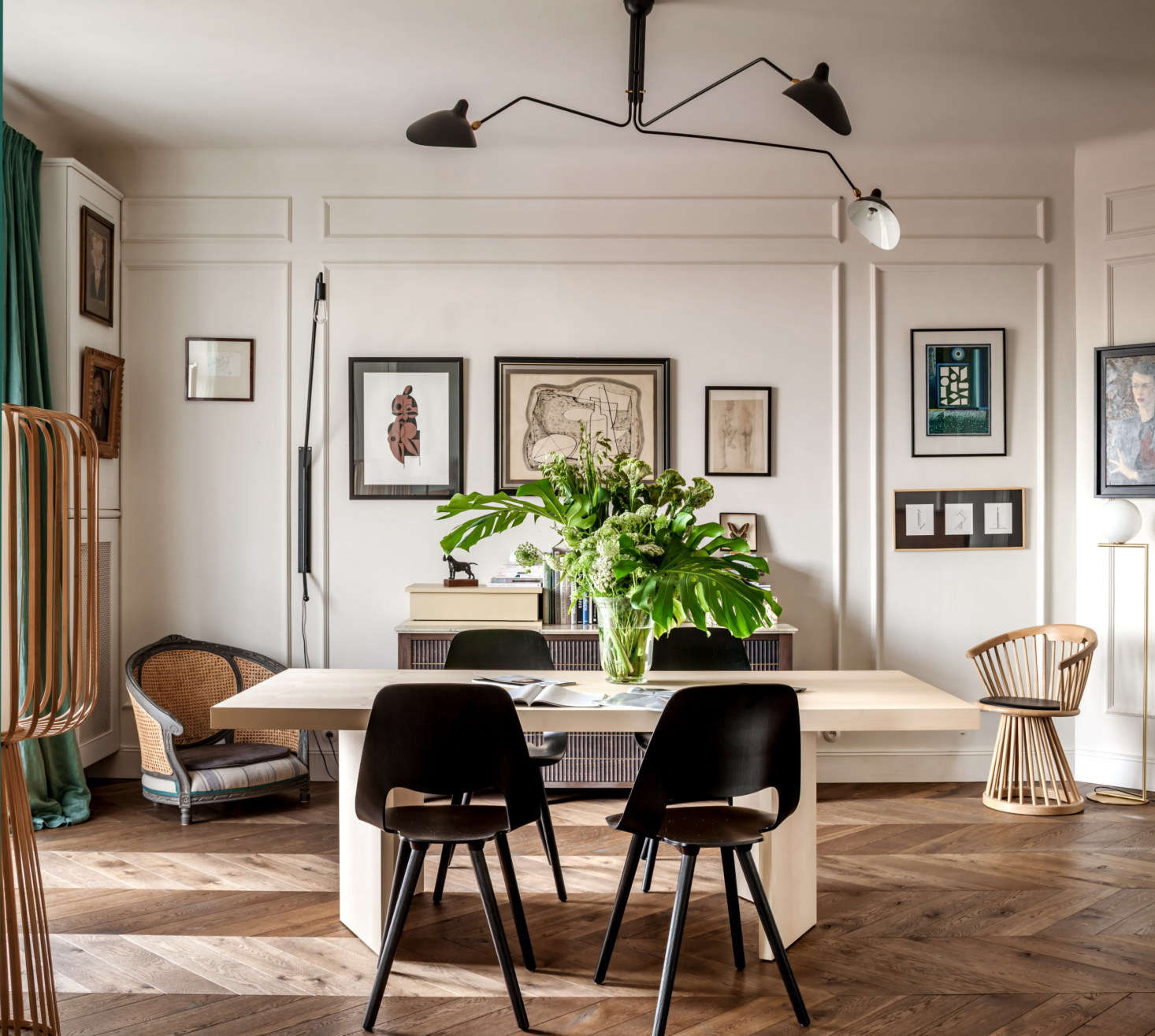 Chrapka and her team designed the dining table, flanked by plywoodVitra chairs, and the sideboard. Much of the art in this room is from eBay. Note the antique armchair, at left, that was cleverly converted into a dog bed.
