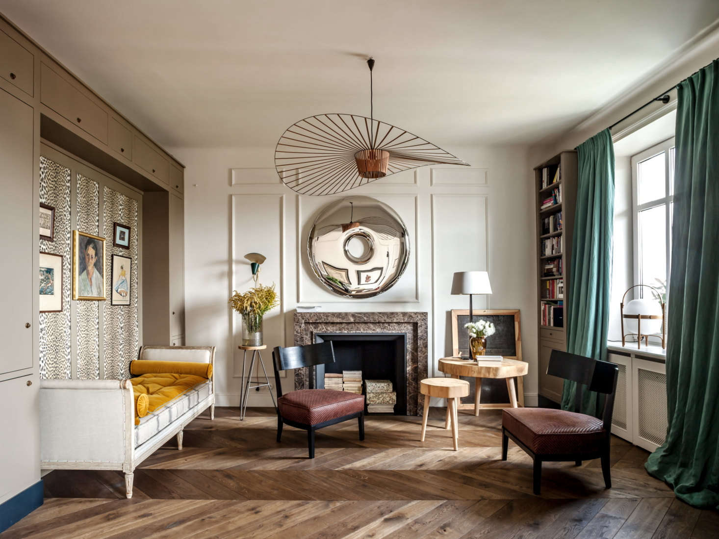 Hovering above the living room is the Vertigo chandelier byPetite Friture. The other showstopper in the room is the round metallic artwork by Polish architect and designerOskar Ziet.