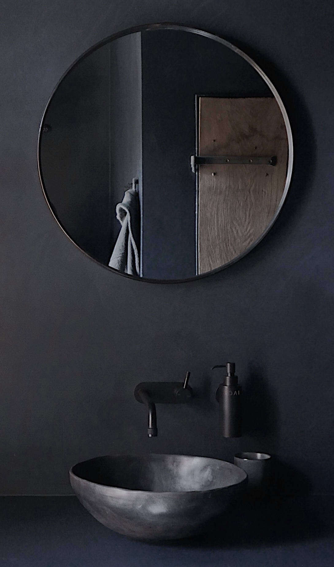 A sculptural ceramic basin from Joris Van Apers paired with a wall-mounted matte-black faucet from Phoenix.