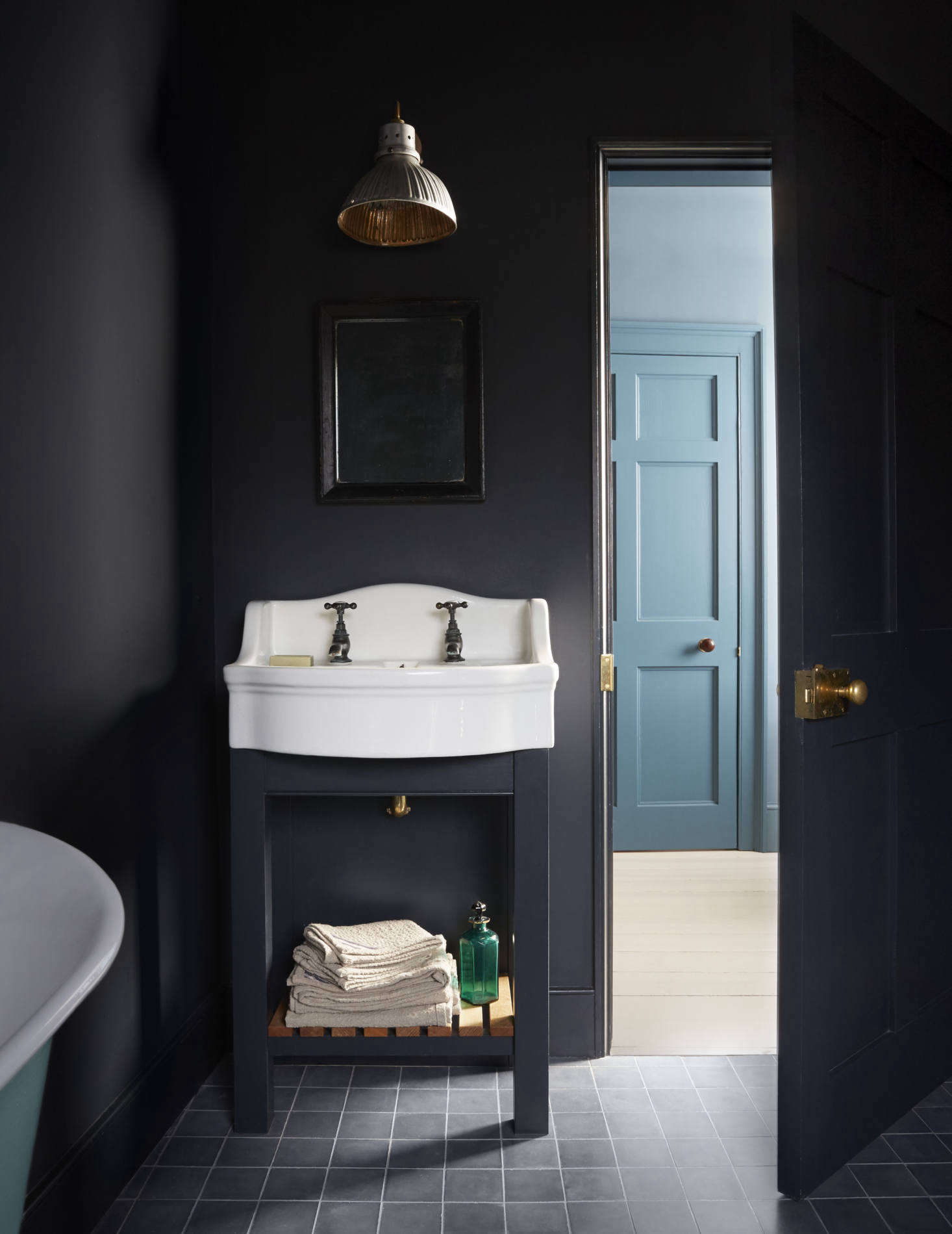"""Harding assembled the guest bath's sink, taps, bathtub, and mercury glass light from """"various antiques shops and salvage yards."""" She painted the room Farrow & Ball Railings and the tub turquoise."""