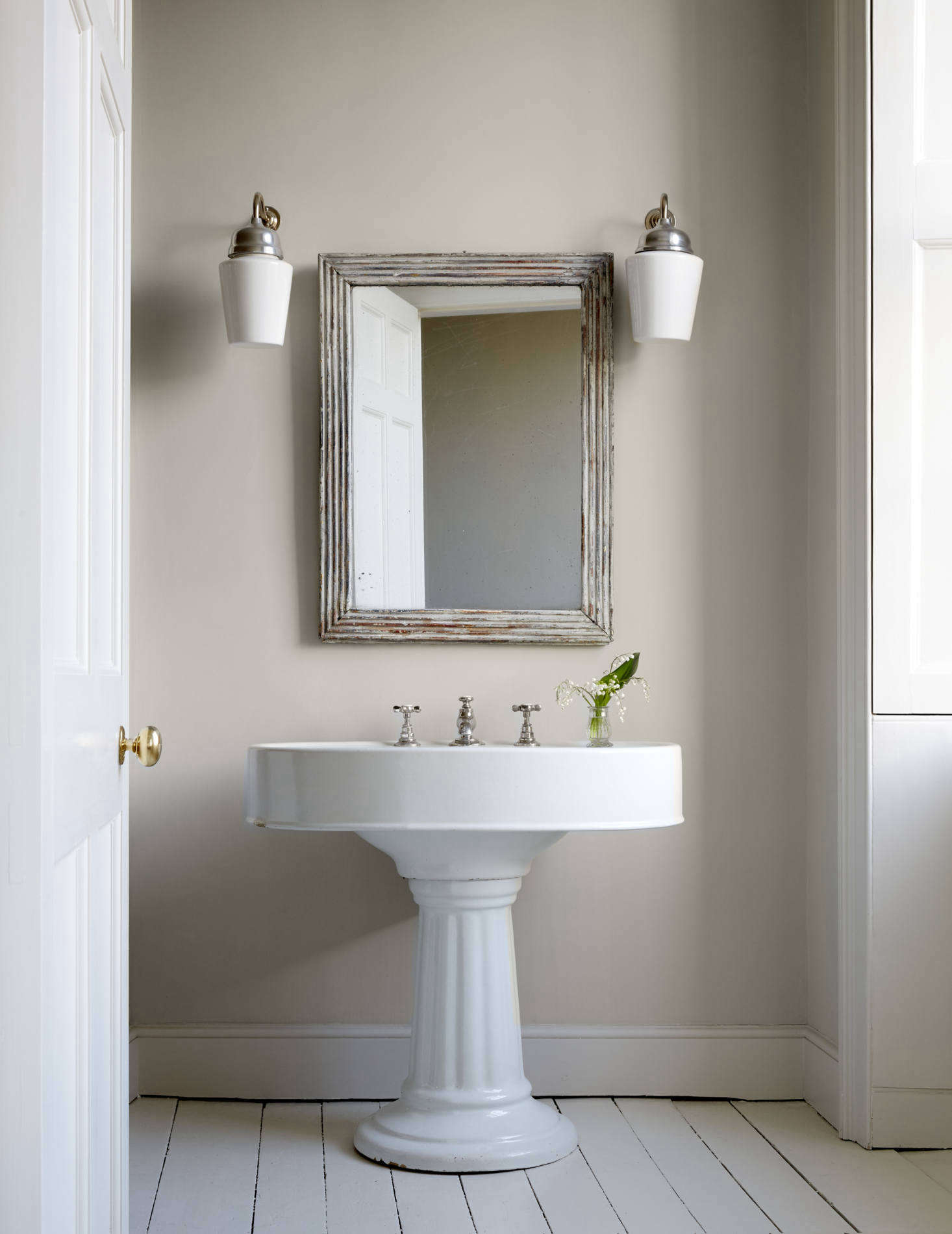 The master bath's stately sink came from a reclamation yard. The mirror is also antique and the Bone China Wall Lights are from Felix Lighting.