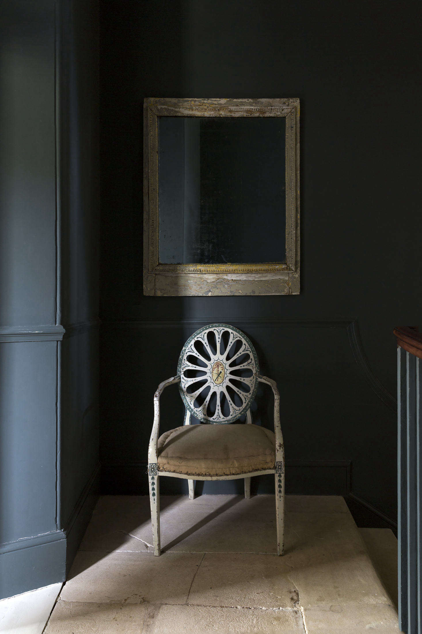 A painted Hepplewhite chair stands on the half landing between the first and second floors