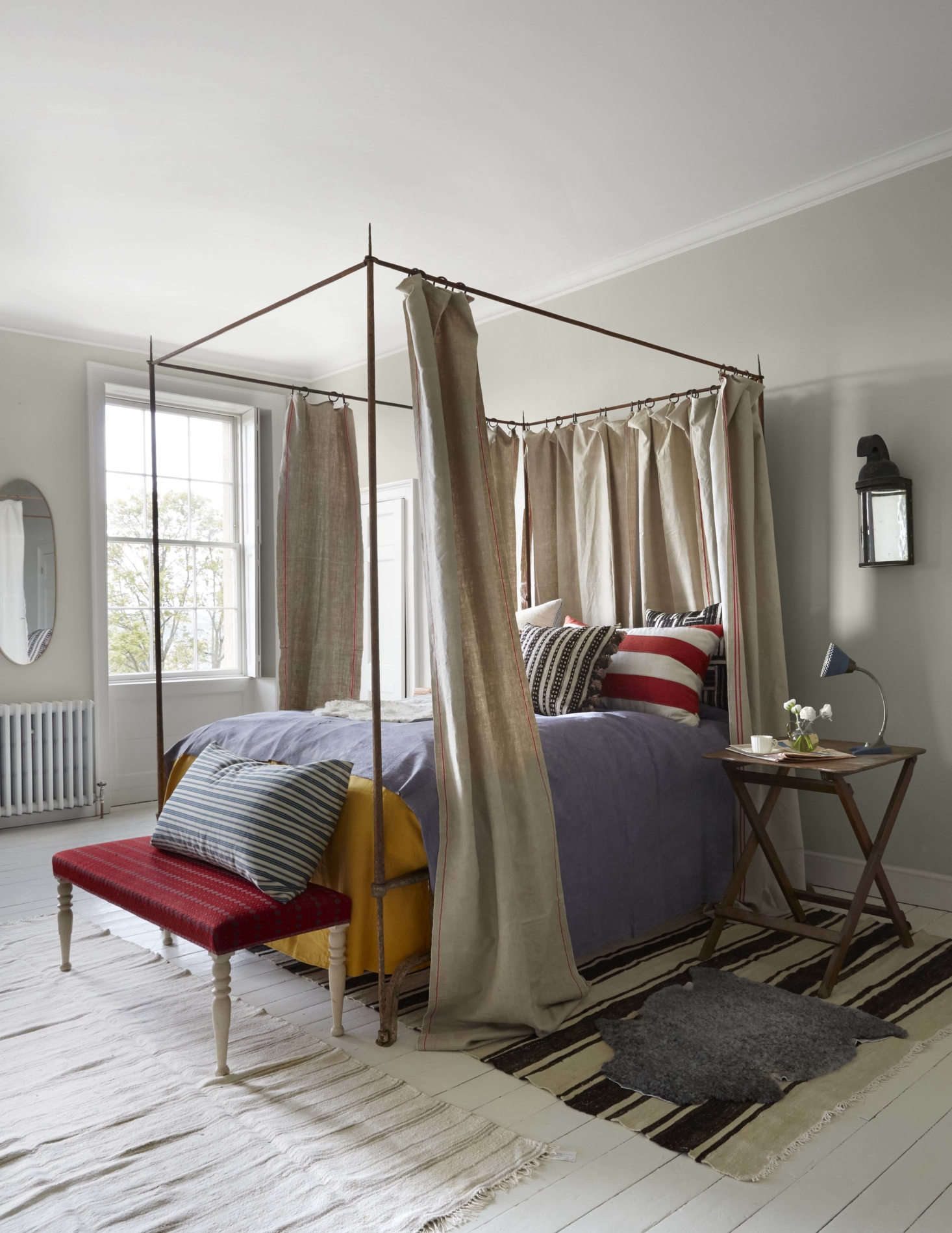 """The main guest room features a canopy bed of wrought iron based on a 17th century Italian original: """"It took me years to find a blacksmith with the skill and courage to make it,"""" Howe tells us. The bed curtains are linen as is the hand-dyed lavender bedspread; both are from Howe's vintage fabrics offshoot,Howe at 36 Bourne Street."""