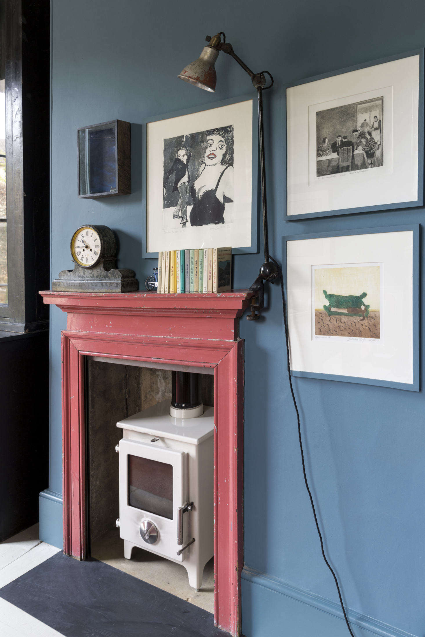 An antique mantel in its original paint was added to the room along with a wood-burning stove and vintage workman's light. Photograph by Claudia Rocha courtesy of Howe London.