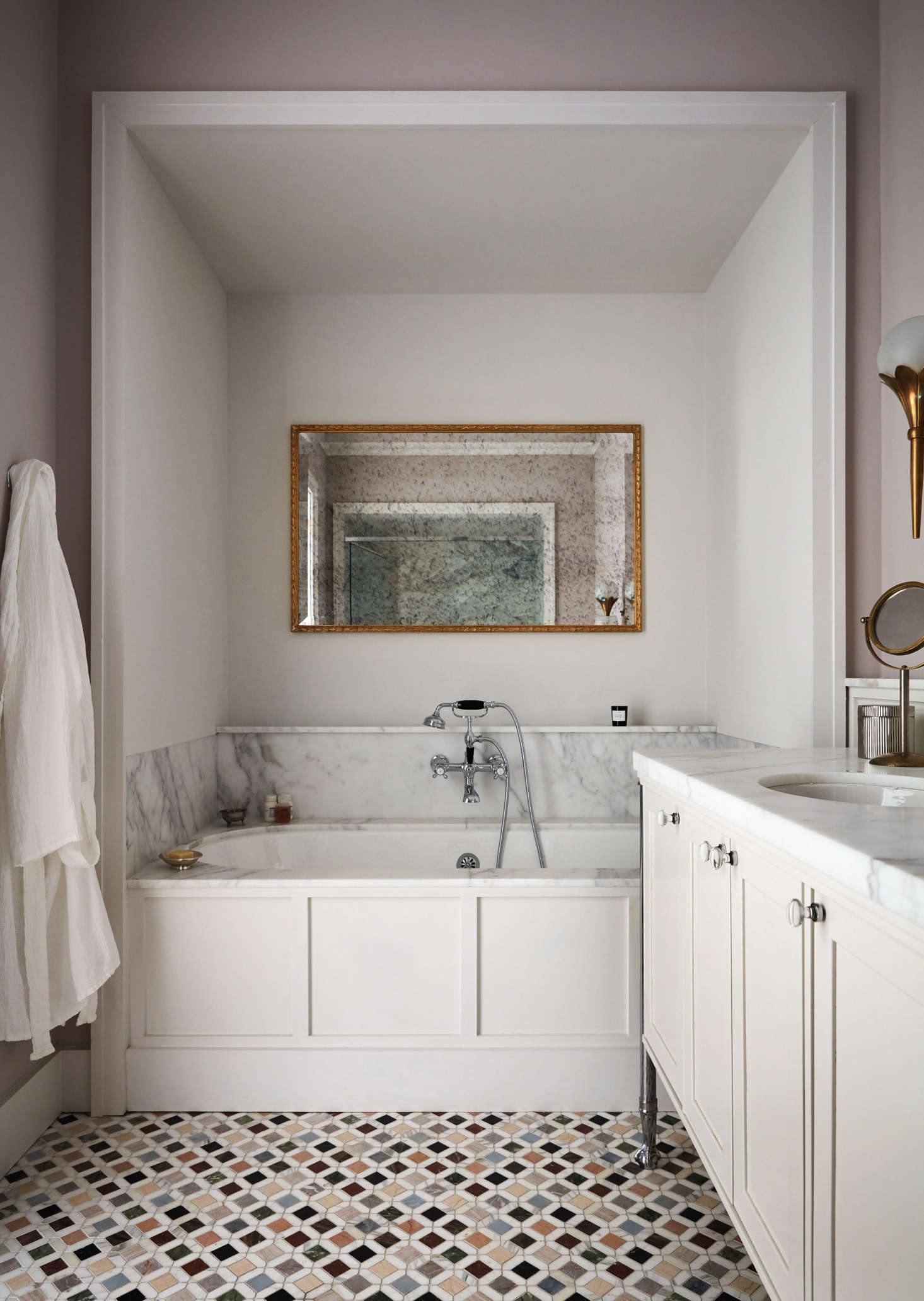 A luxe bath, with a marble tub surround (and slim ledge, for storage) and a mirror with antiqued glass.