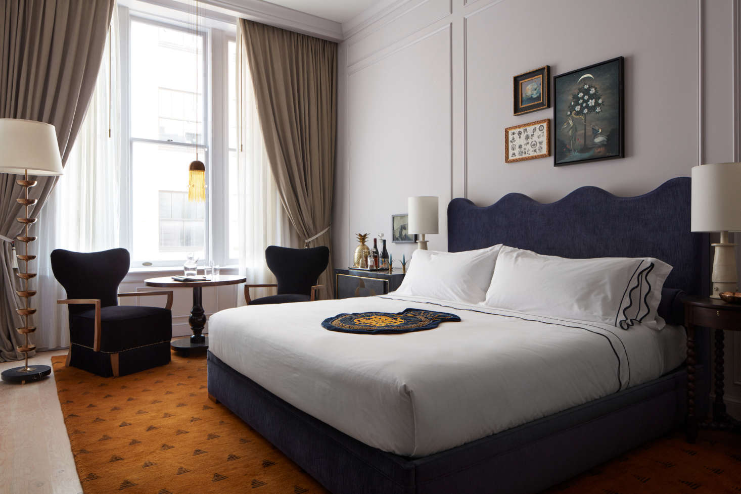 Guest bedrooms feature ochre-colored rugs, muted walls, and glam fittings.