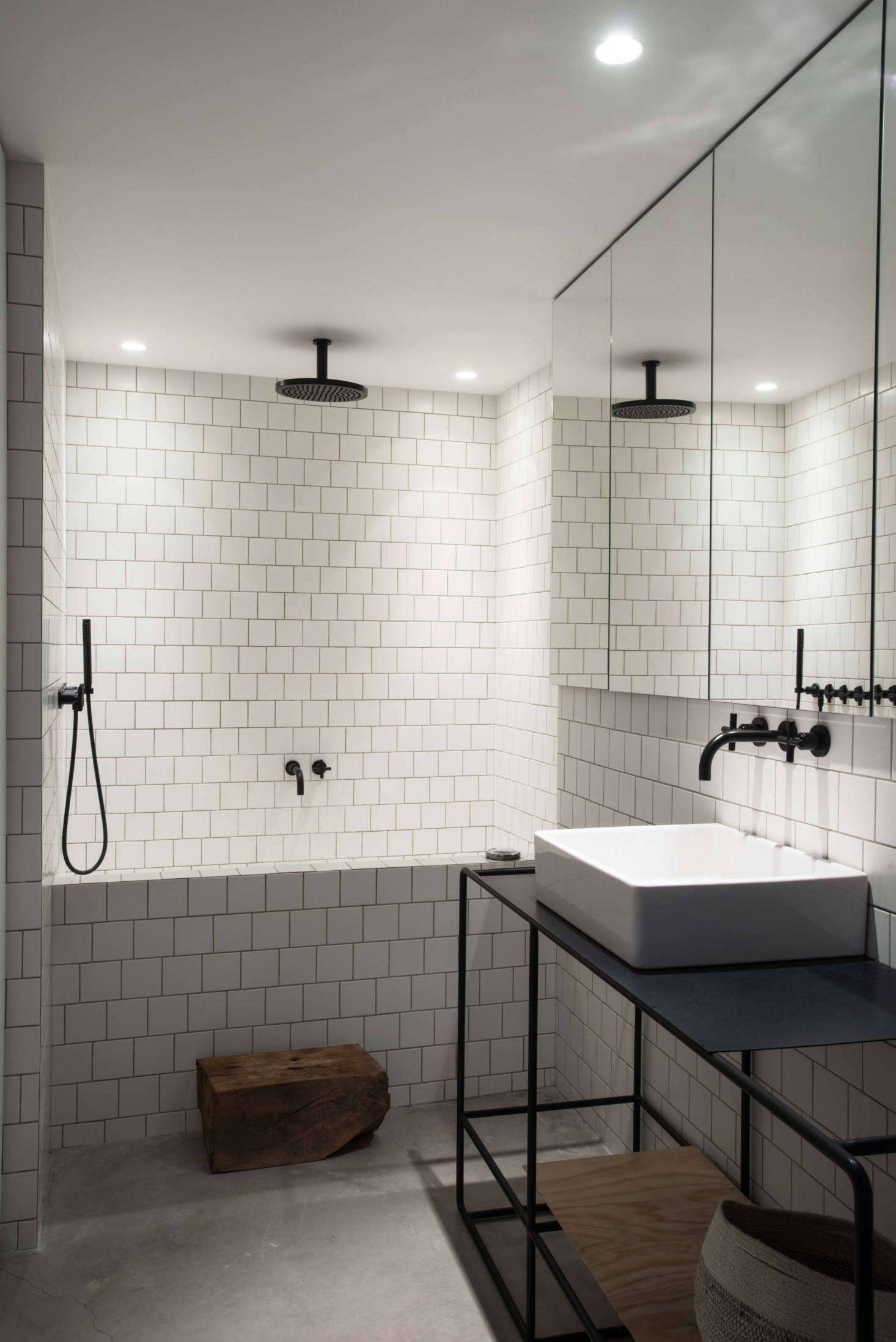 Villeroy & Bosch Pro Architectura classic square tiles line the black-and-white master bath, including the tub surround. The steel sink frame is a custom design and the black faucets and shower hardware are by Duravit.