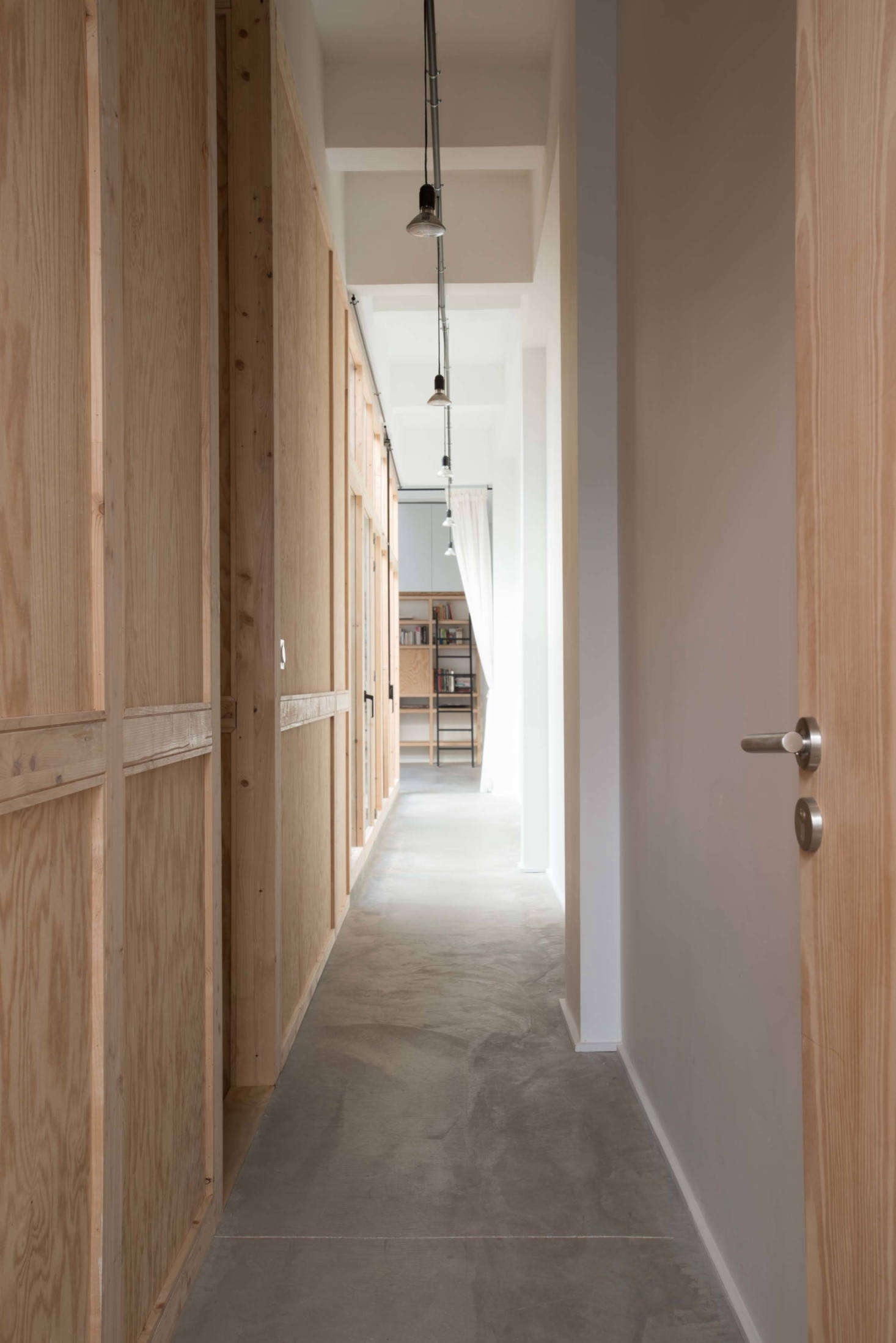 Just off the entrance, a plywood hallway leads to the open-plan living room.