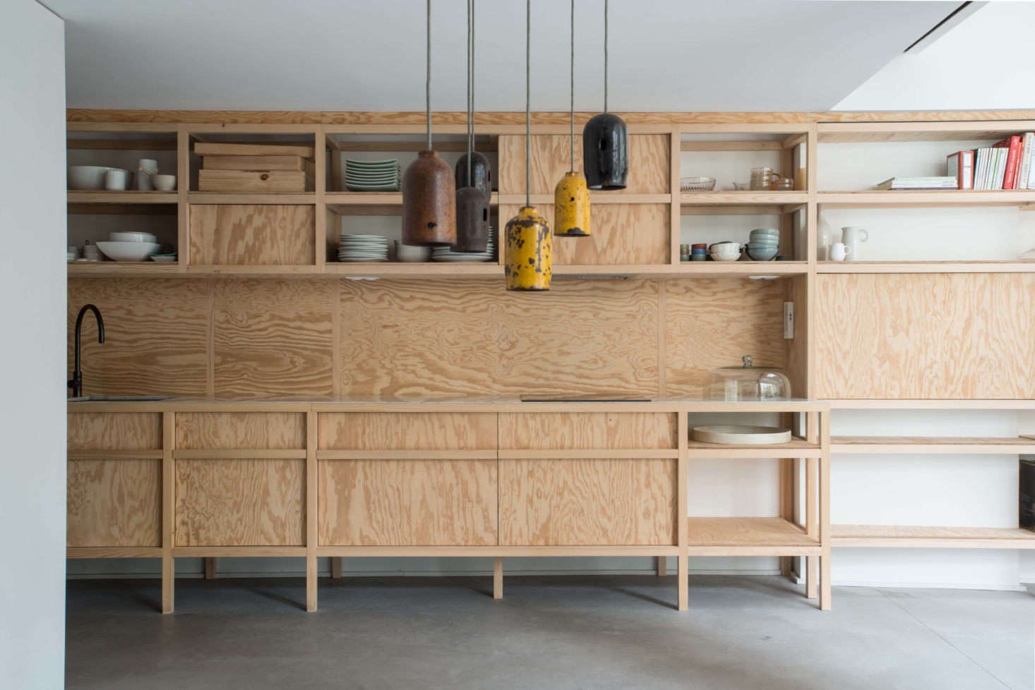 At the far end of the space the shelving morphs into an all-wood kitchen.