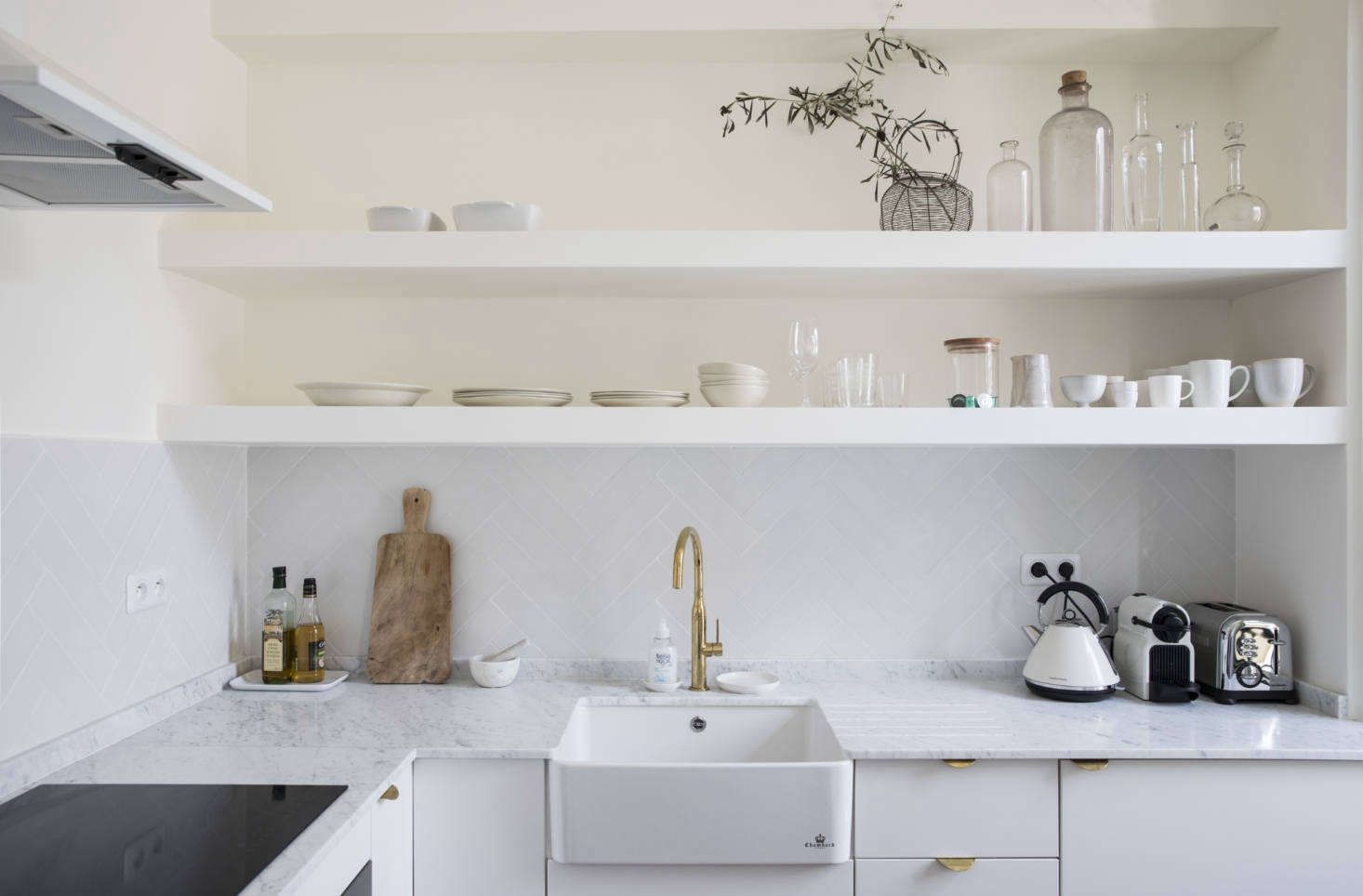 The farmhouse kitchen sink is from Darty and the white extractor hood is from La Peyre. The counters are Carrara marble sourced from Marbrerie Provencal.