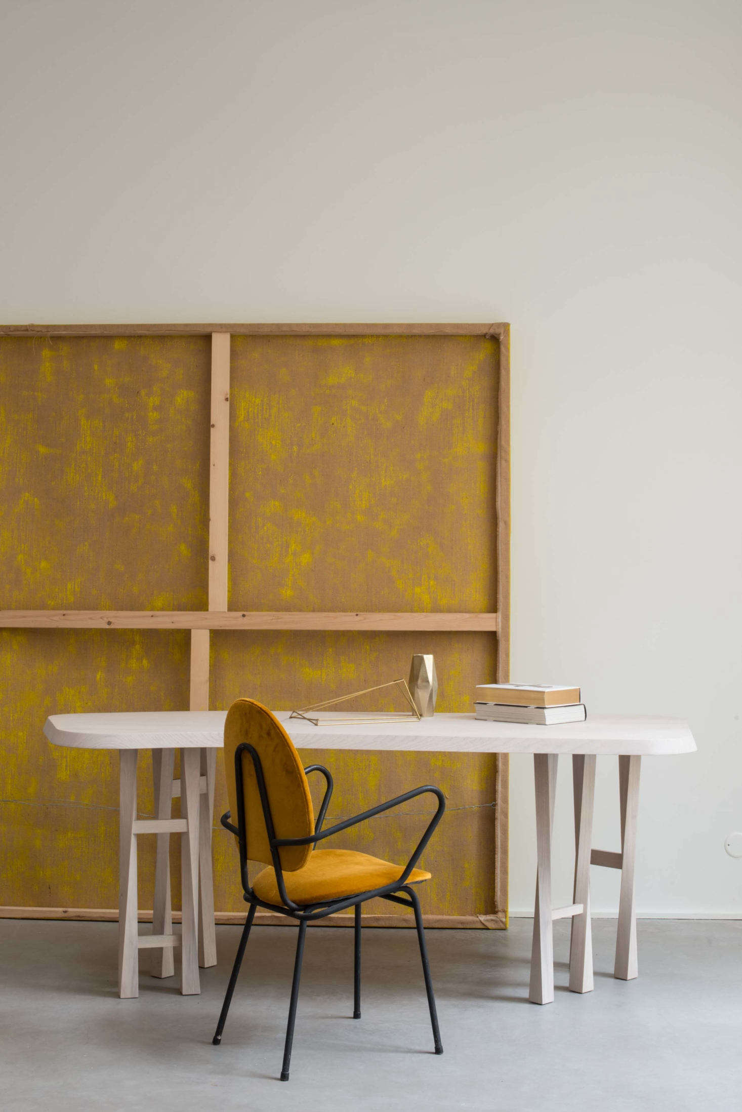 A canvas stretcher turned back to front echoes the plywood paneling throughout. The desk is Christophe Delcourt&#8