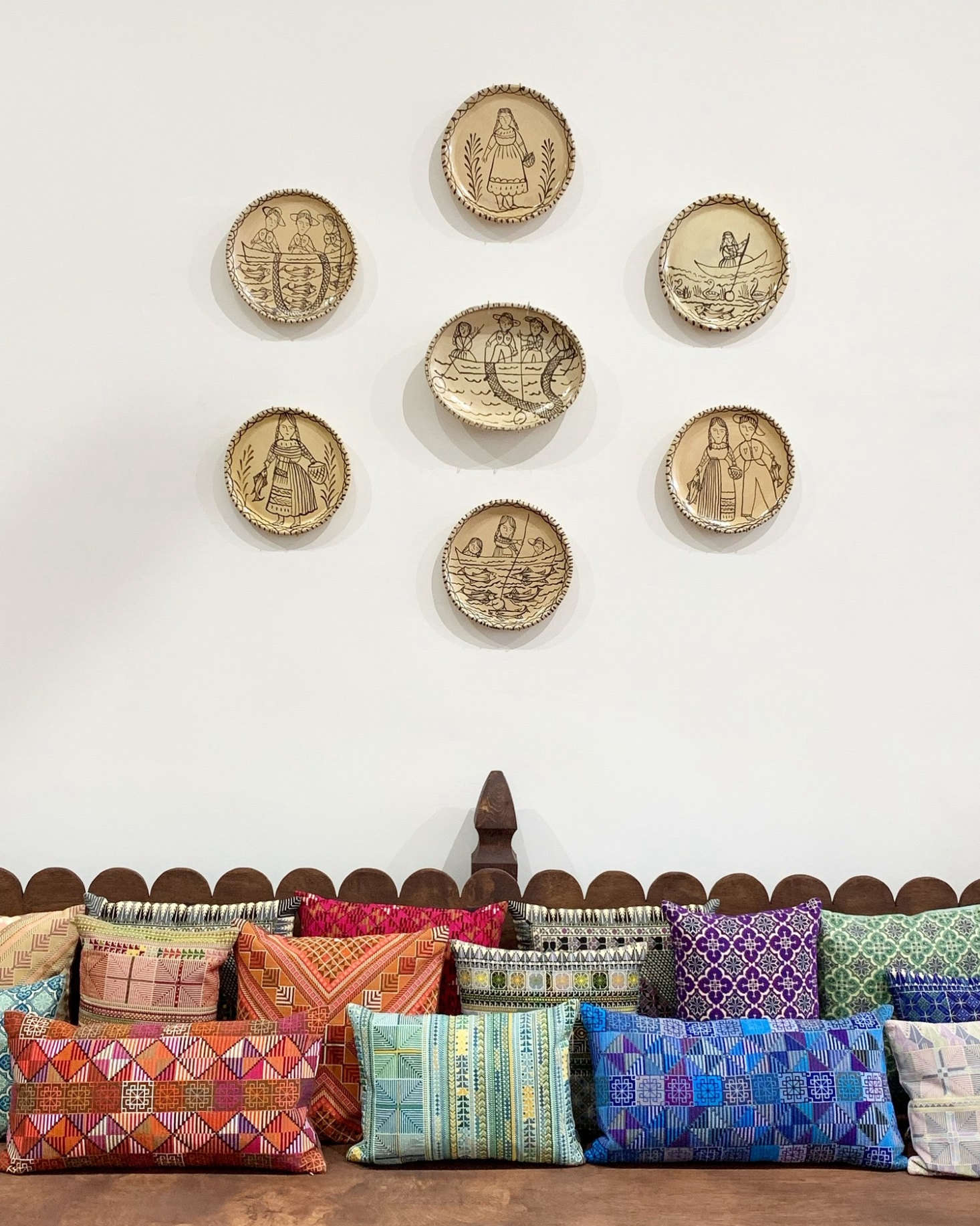 """We've been admiring """"plate walls"""" adorned with matching plates from a series (shown above, a collection ofvintage plates from Michoacán are mounted above a collection of Kissweh Pillows pillows at a recent Kneeland Pop-Up in Los Angeles) or a mix of collected pieces. (Also seeBugandé Cafe: A Moody, Eccentric Restaurant in Milan, where even the ceilings are adorned with plates.)"""