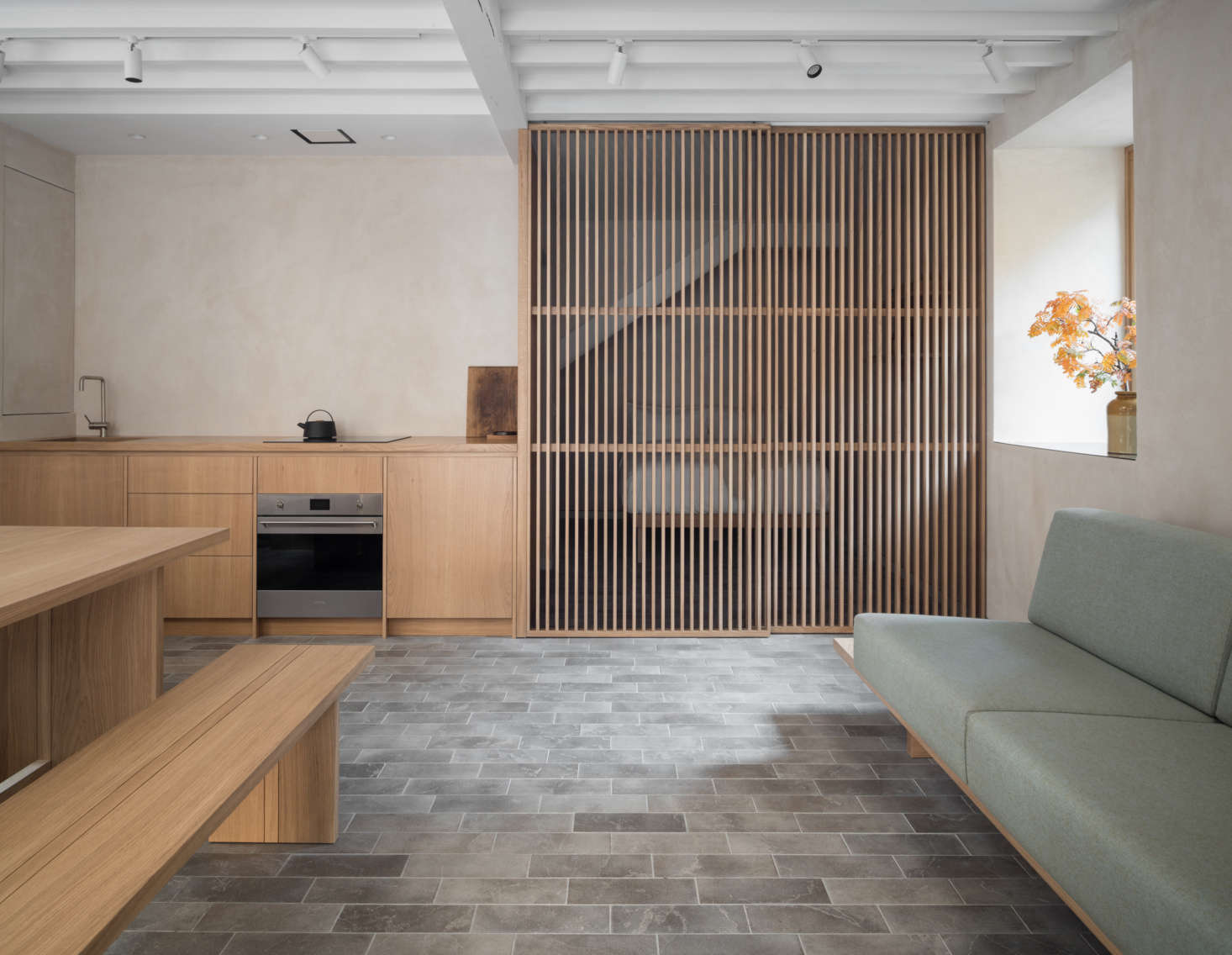 The gray limestone tiles—with radiant floor heating—echo the cobblestones outside. In the back of the room, a second slatted wood screen divides the bedroom from the rest of the quarters.