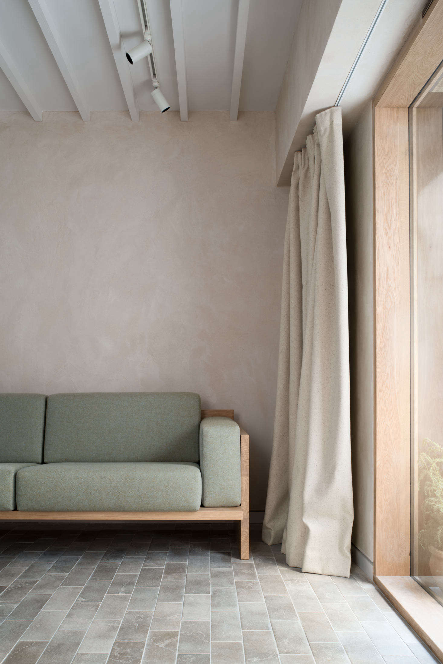 Heavy canvas curtains can be pulled across the entrance. The couple finished the walls with clay plaster from Clayworks to enhance the light, regulate humidity levels, and create a surface so nuanced there&#8