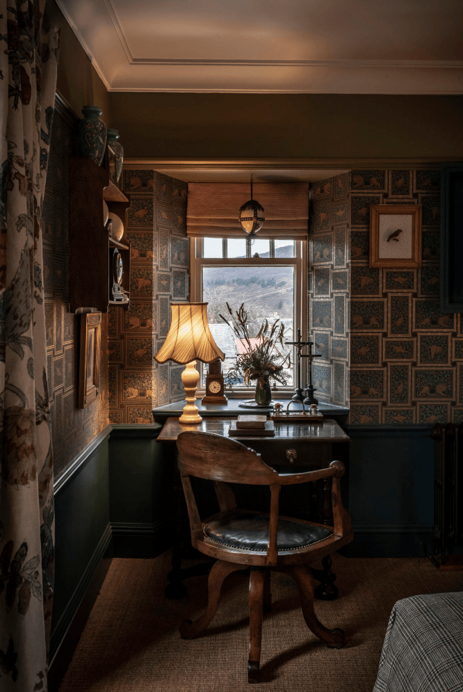 A vintage desk looks out at the countryside in another room.