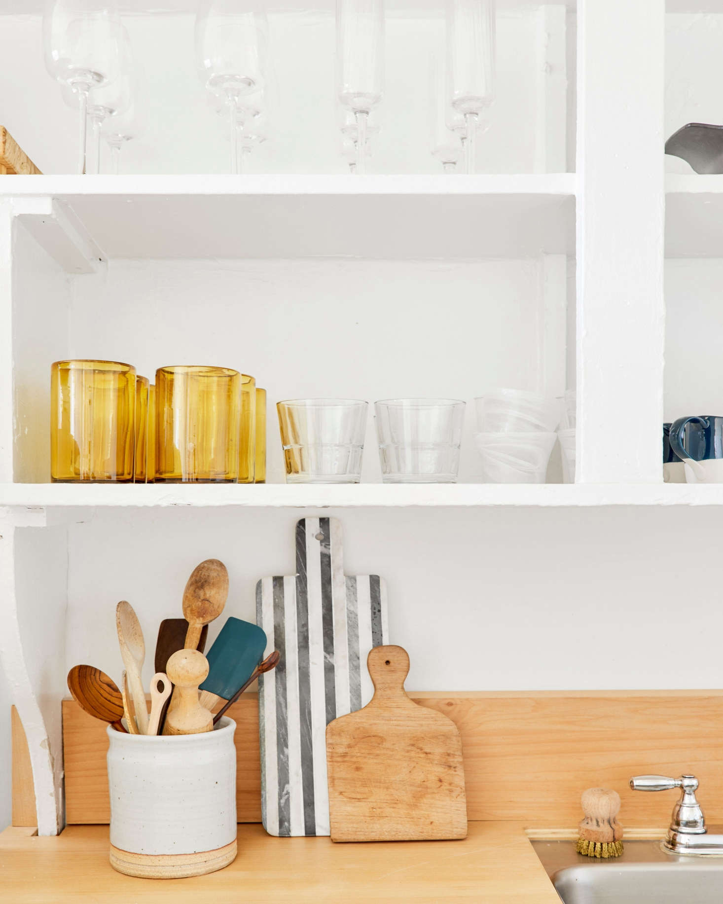 """Jessica didn't have to do much to the kitchen cabinets. """"I just replaced the hardware on the lower cabinetry, but the uppers came that way! When I looked at the place for the first time, my heart stopped when I saw all the open shelving. In my head I thought it was the perfect excuse to buy only beautifulkitchenwaressince they would be on display all day, every day,"""" she says."""