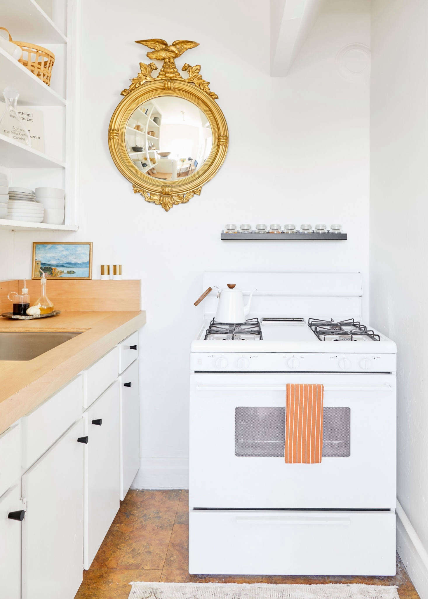 """Jessica chose Farrow & Ball's Pointing for the walls—""""the most perfect warm white."""" She's not sure what's on the cabinets, as they were painted before she moved in. Jessica considered making over the linoleum floor with sticker tiles, but its unevenness would have made that difficult. Instead, she made do by covering much of the floor with a vintage Turkish rug. The mirror has been in her family for four generations. The landscape was a $20 flea market score. (SeeThe New Art Gallery: 12 Favorite Kitchens with Paintings on Display.)"""
