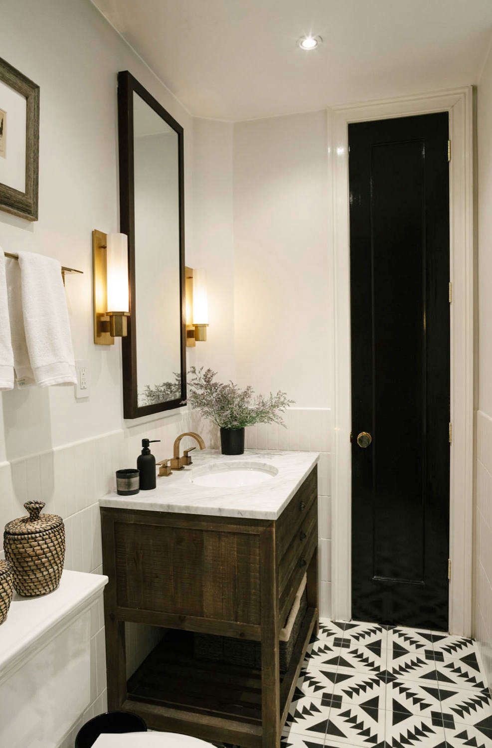 The bathroom features a stone-topped vanity fromRestoration Hardware. Above it are Argon Sconces from Hudson Valley Lighting and a custom mirror. Tiles from Cement Tile Shop form a graphic pattern.