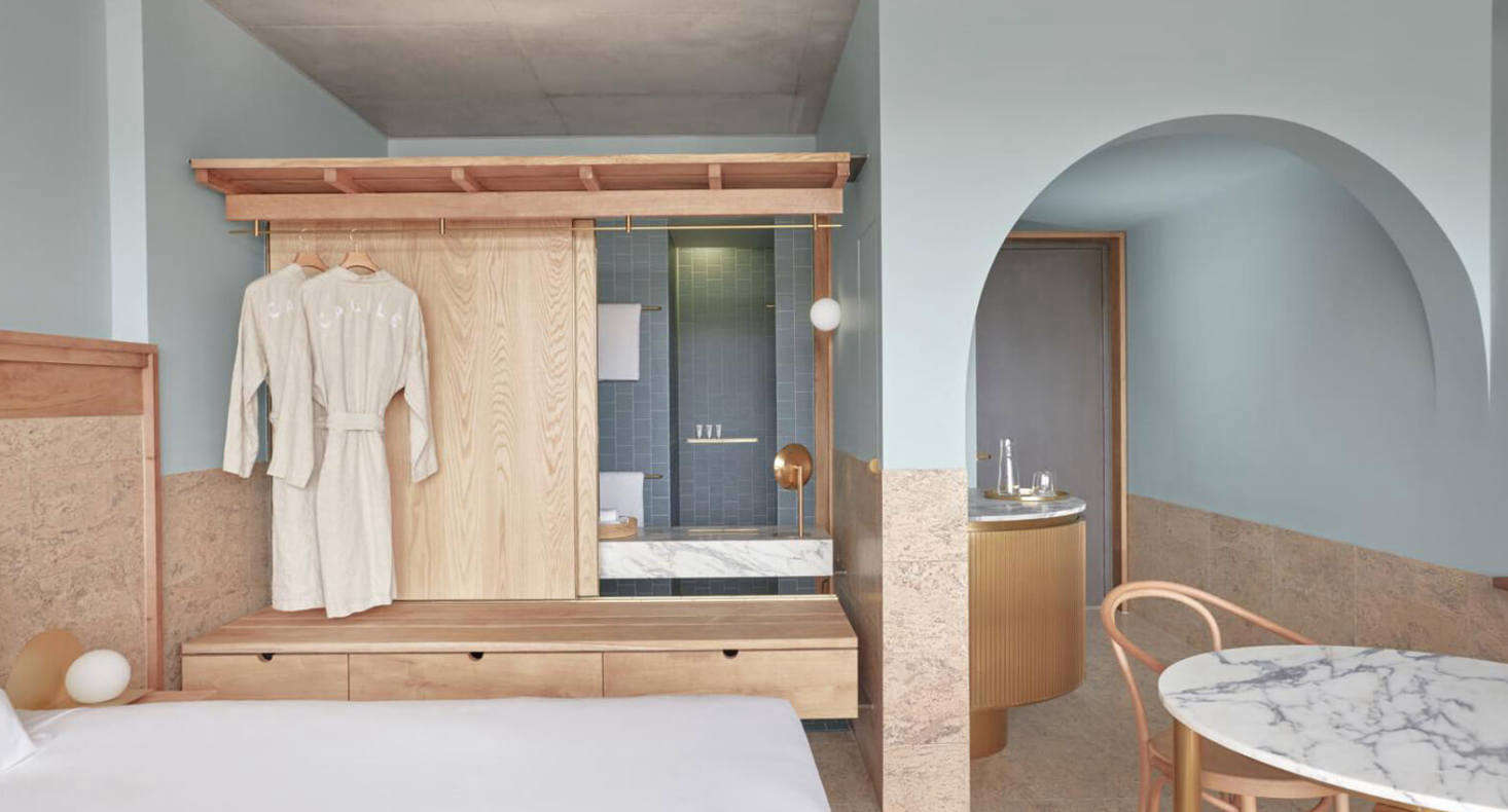 In each guest room, the floors and lower half of the walls are paneled in cork. An inventive small-space idea, shown here in an Urban Terrace Room: a plywood built-in serves both as clothing storage and as a divider between bedroom and ensuite bath (on the bathroom side, the plywood is fronted with mirrors). The panels slide to allow openness between the rooms.