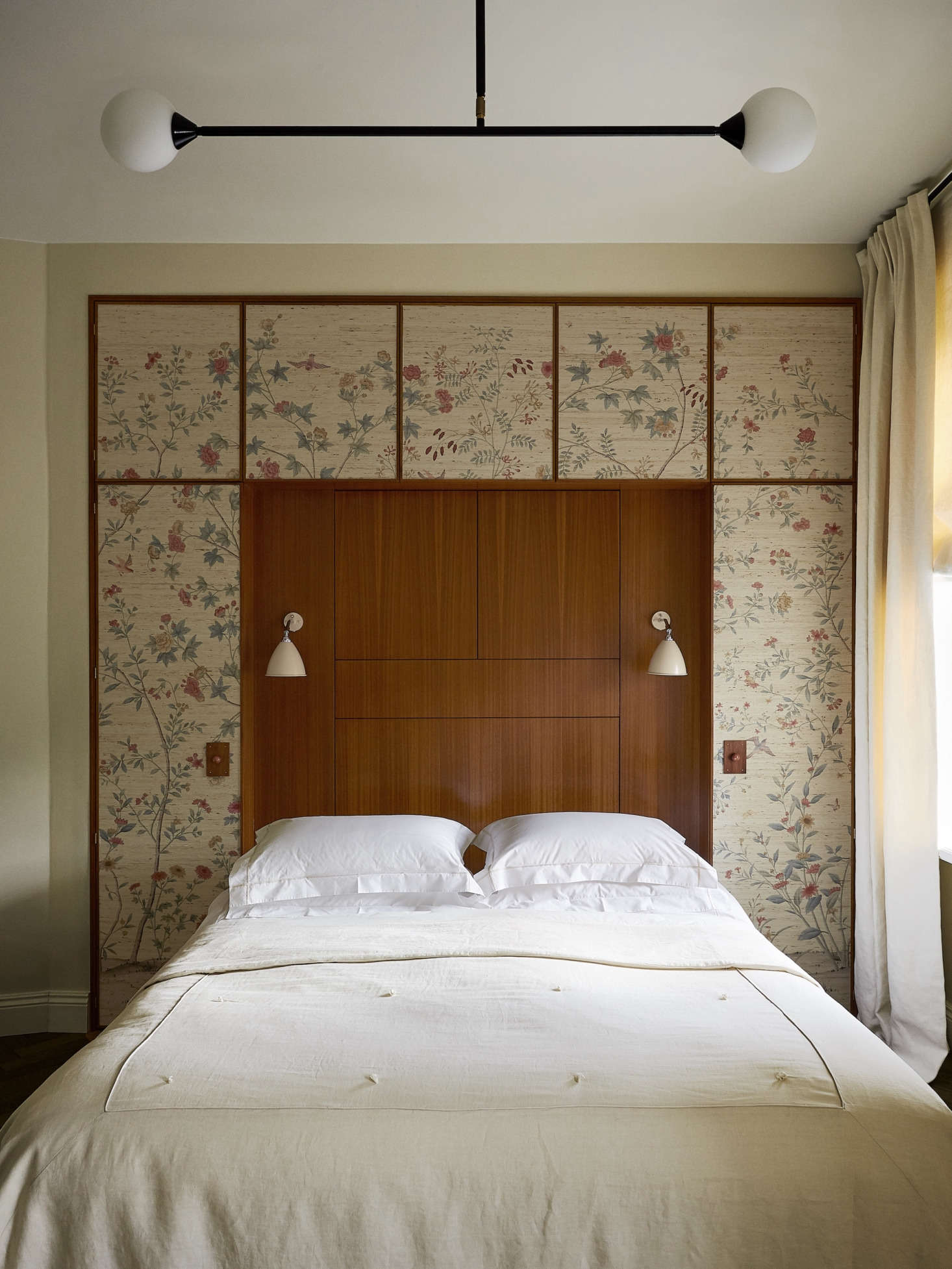 A quirk of the apartment is that nearly every room has a diagonal wall. In the bedroom, Chrapka straightened the room with the help of a built-in headboard and cabinet, covered with William Morris wallpaper. The Bestlite sconces are by Gubi.