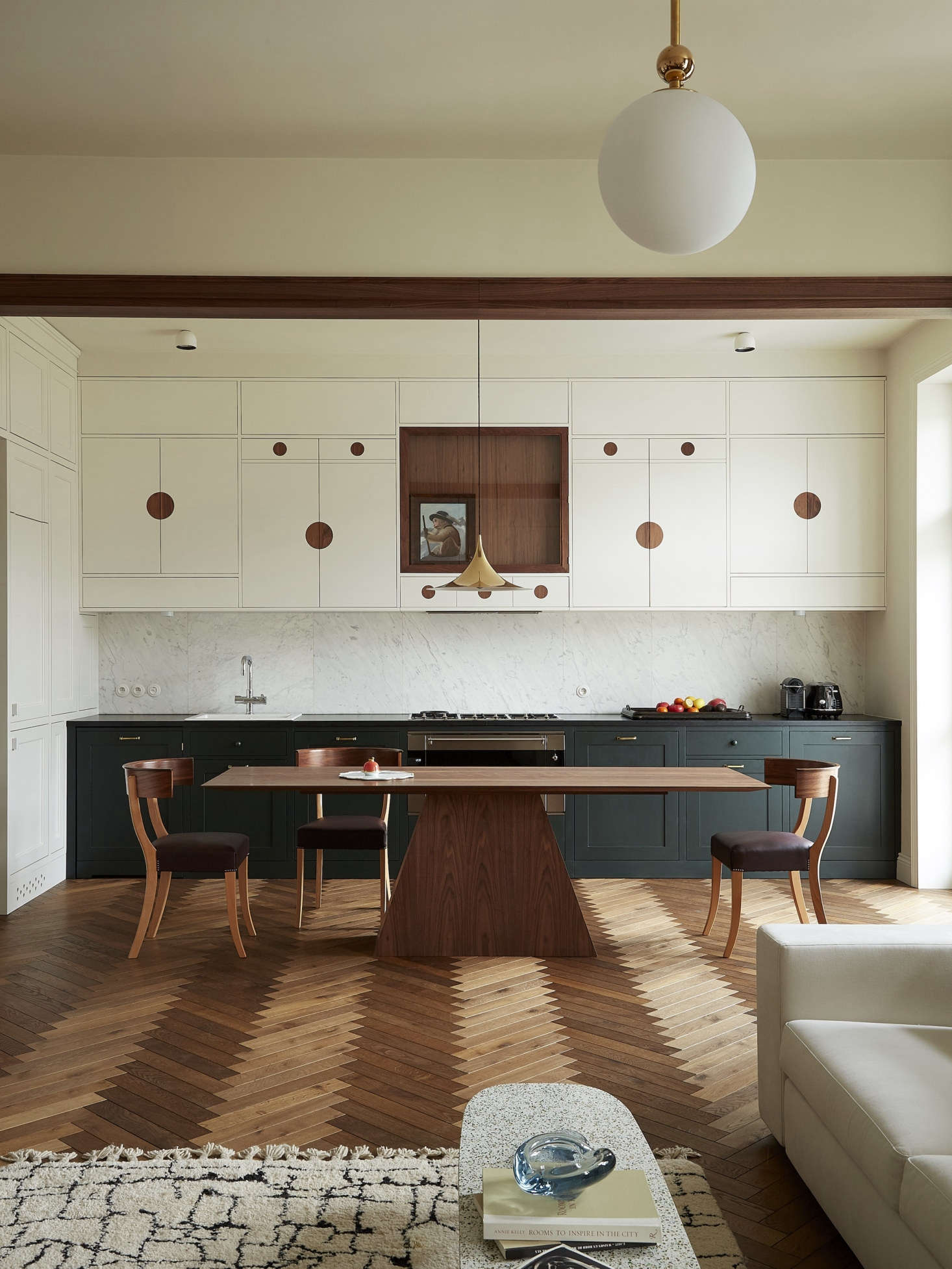 The kitchen, open to the living room, was inspired by a Josef Frank-designed sideboard featuring walnut discs and glass doors. &#8