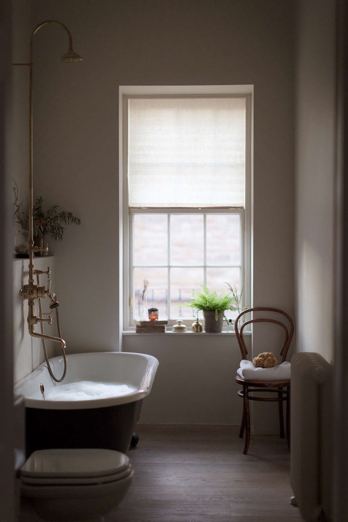 The couple converted a bedroom into the master bath. The new roll-top bathtub was purchased from C.P. Hart and painted Farrow & Ball&#8
