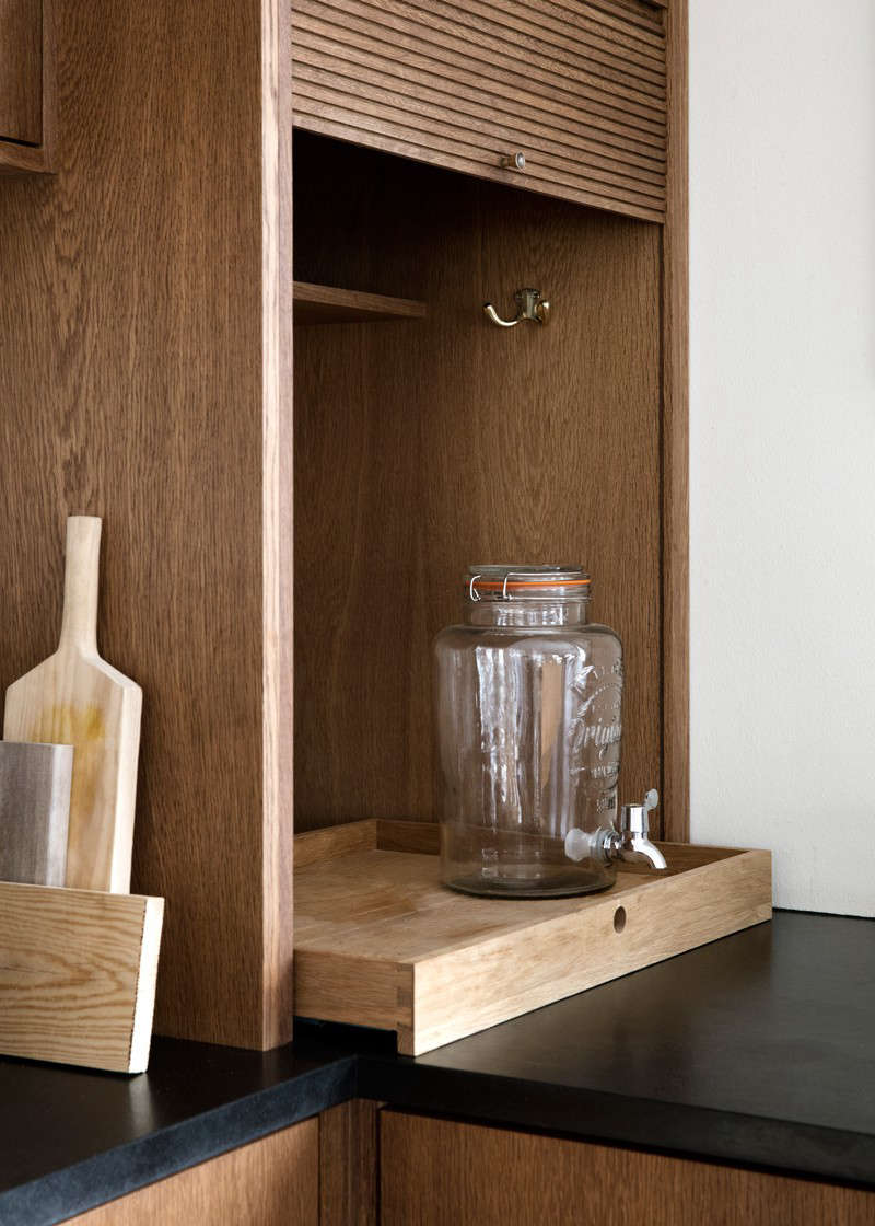 """""""When the cupboard is pulled up, there's space for our kitchen machines and equipment on a pullout tray—very practical,"""" says Rebecca. (For drinks dispensers like this one, see 10 Easy Pieces.)"""