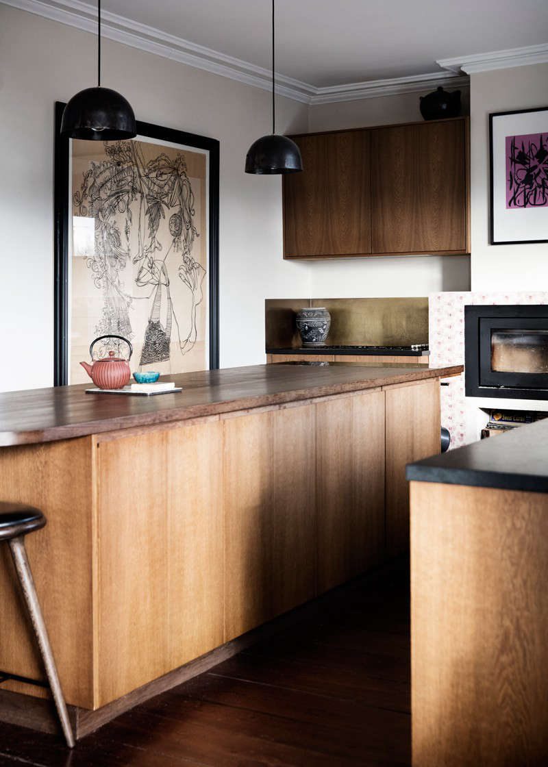 """In the back corner, the stove and cooktop are set off by a patinated brass backsplash. The couple selected a variety of drawings and paintings to display. To those concerned about grease and grime, Rebecca says, """"everything near the stove and fireplace is behind glass.We think it's important to 'use' art."""""""