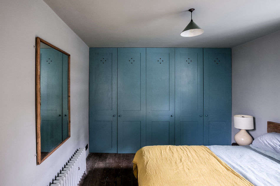A wall of blue closets anchors this bedroom.