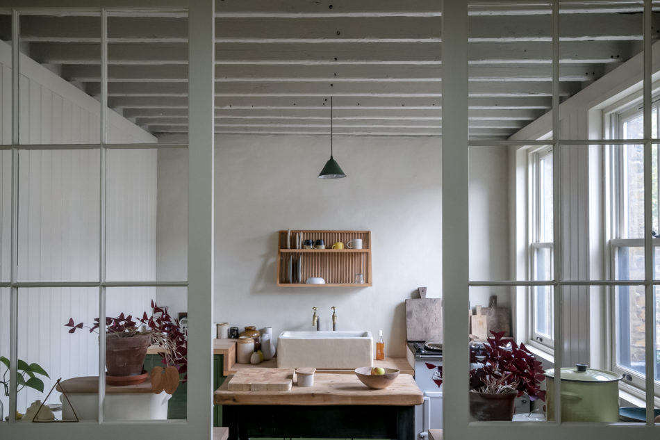 The house is just 8 square feet and has two bedrooms. Here, a peek into the kitchen from the dining area. A dark green pendant light matches the green lower cabinets. The counters are oak and the sink is hand-cast concrete. (Like the plate rack? See Drip Dry:  Kitchens with Wall-Mounted Dish Racks for more examples.)
