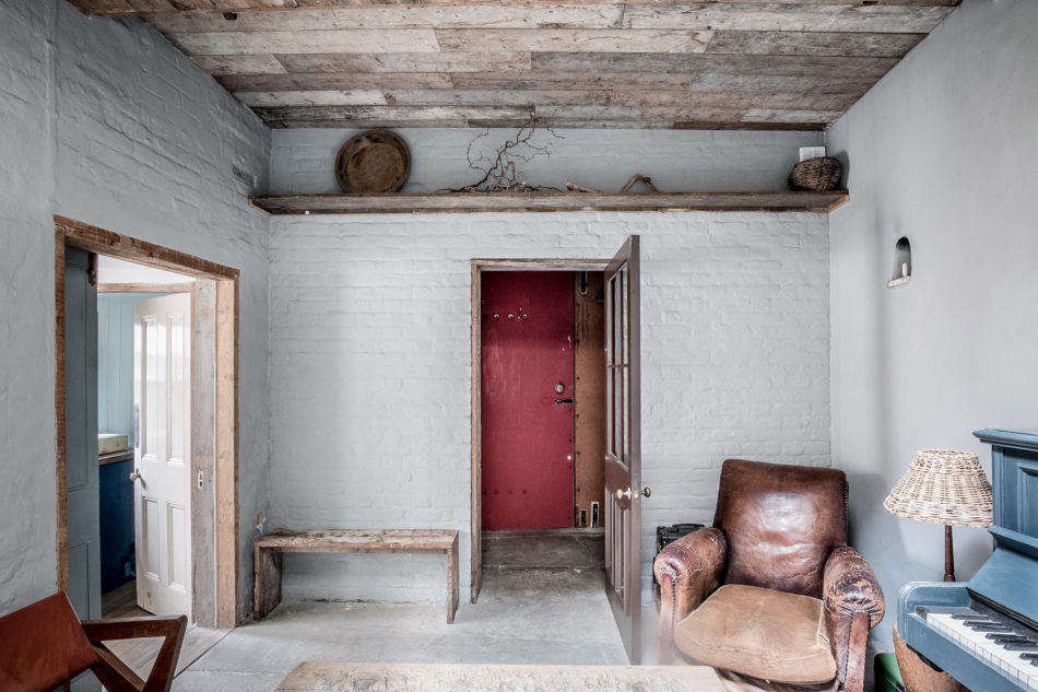 The entryway (painted red) leads into the living room. Painted brick walls and concrete floors add to the rough-hewn beauty of the interiors. (Note the arched nook in the wall, at right: It was where coachmen kept their candles when working at night.) Just to the left is a powder room.