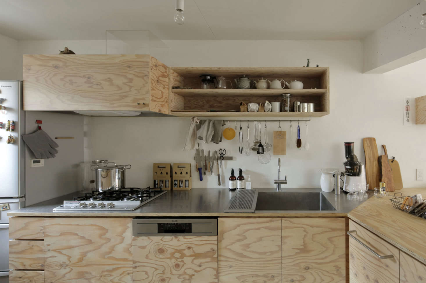The cabinets are faced with lauan plywood finished with a translucent white Osmo Wood Wax, and the counters are a combination of thin stainless steel and plywood.