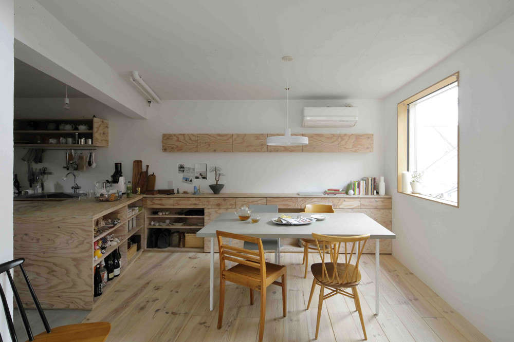 The kitchen—with two long counters that extends out from the sink—opens to a combination eating area and living room set off by wide-board pine flooring. No. 555 designed the concrete-topped table and surrounded it with an odd lot vintage chairs. The narrow cabinet on the back wall contains Mio&#8