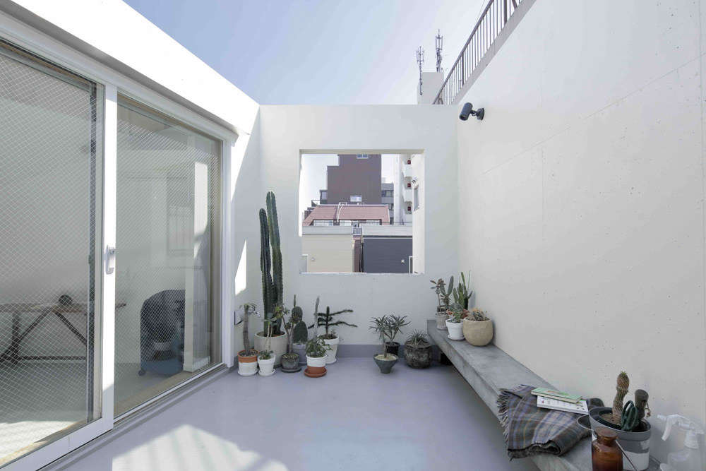 The whitewashed roof deck features a concrete bench and a framed view. Mia told us friends have commented that it reminds them of the roof terrace in the Luis Barragán house in Mexico City.