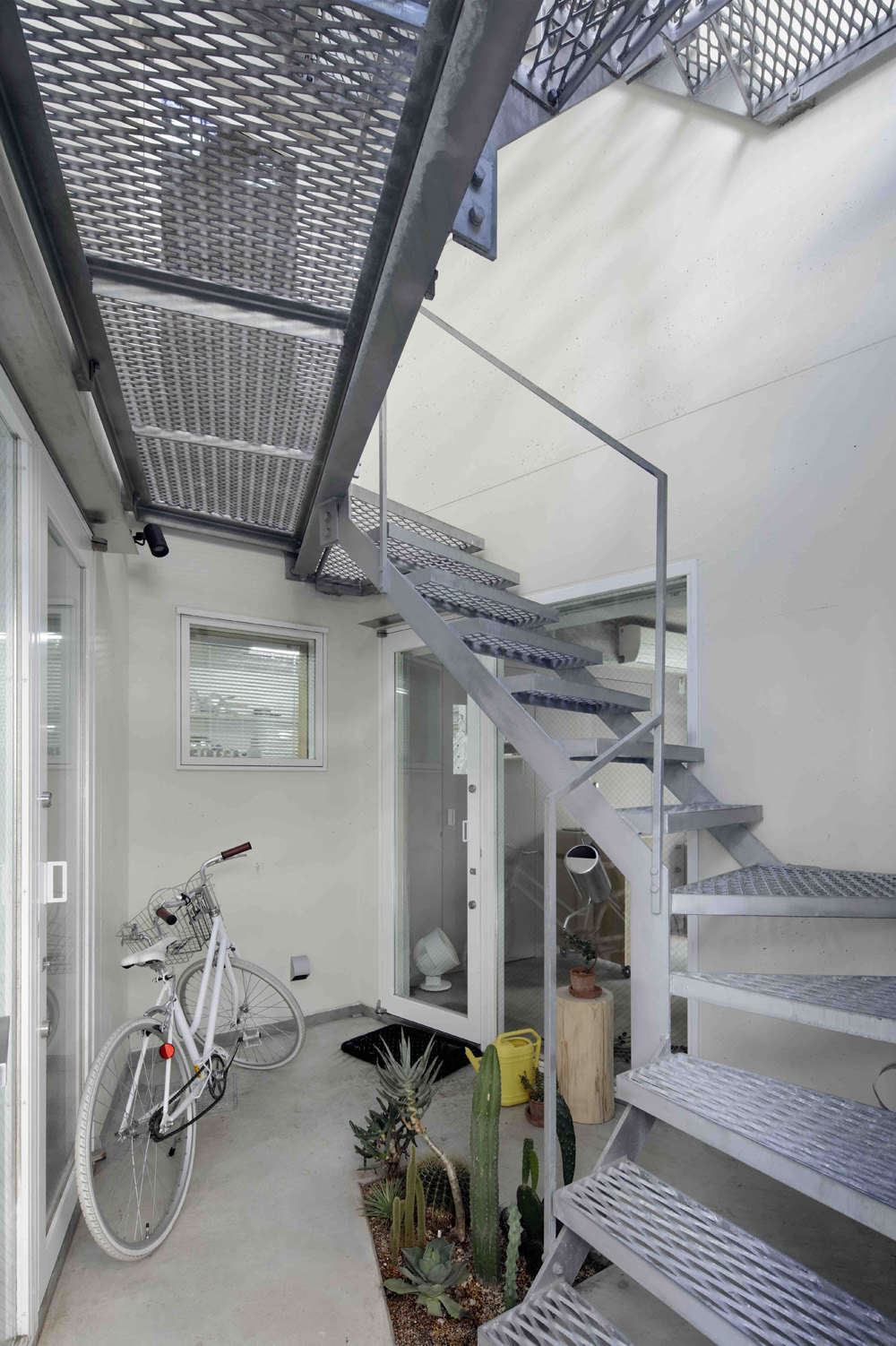 The entrance next to the garage opens to a pocket-size succulent garden next to the steel mesh stair.The ground floor houses a commercial kitchen and showroom for Cineca, Mio&#8