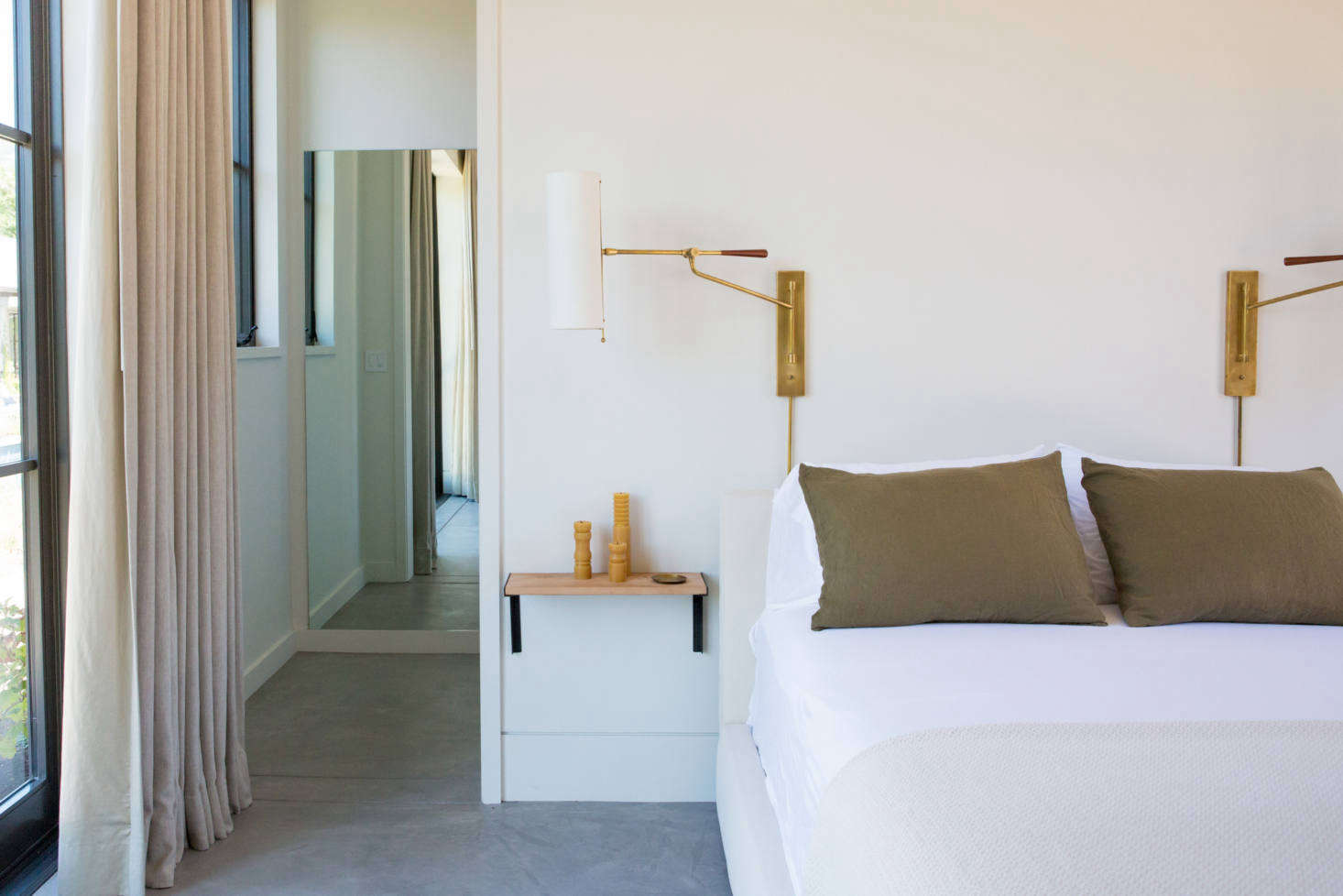 A guest bedroom, with olive-colored pillows found at Napa Valley Vintage Home and a pair of Frankfort Articulating Wall Sconces.