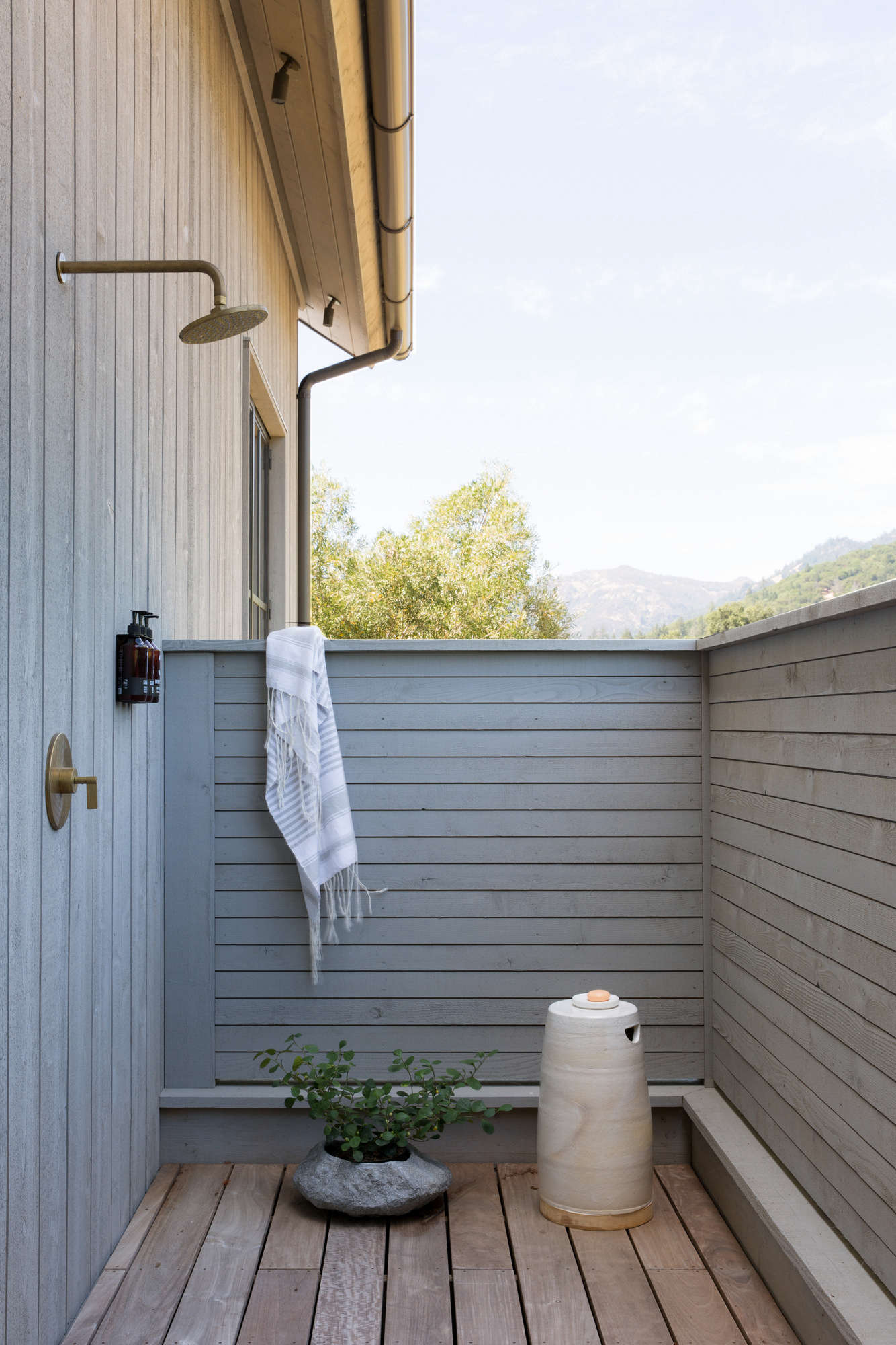"""Just off of the master bathroom is a private outdoor shower, with half-walls, so """"you can watch the neighboring horses graze,"""" Geremia says."""