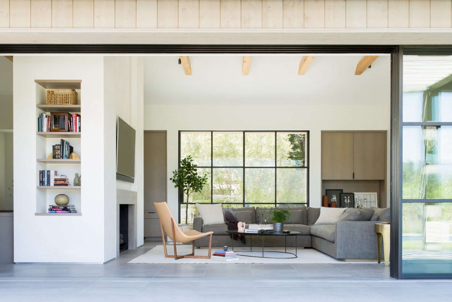 """Another living area with low-slung furniture and natural wood beams. """"The organic and wood elements are casual, tactile, and intimate and serve to underscore a sense of place,"""" Geremia says."""